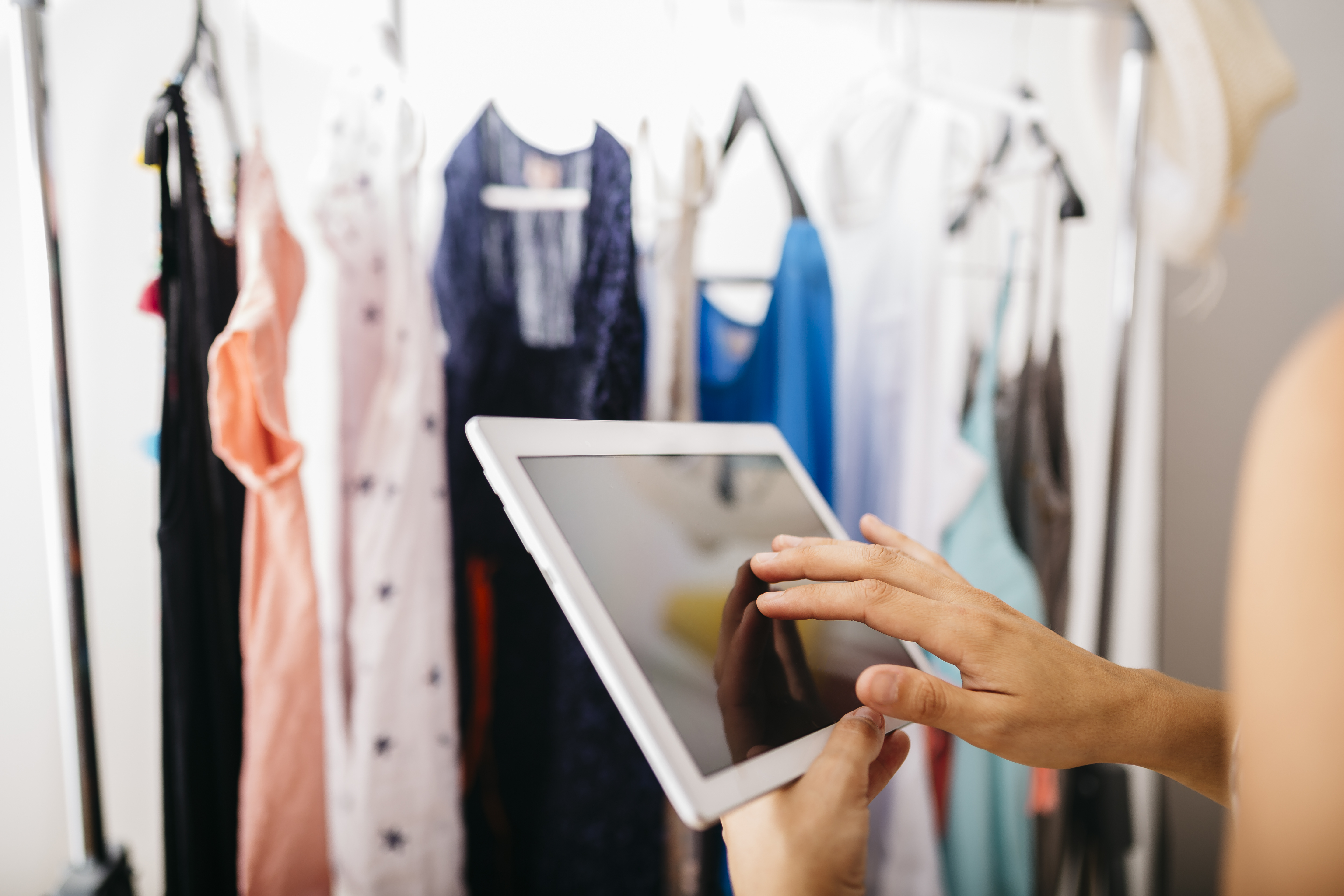 Woman holding tablet in front of closet full of clothes