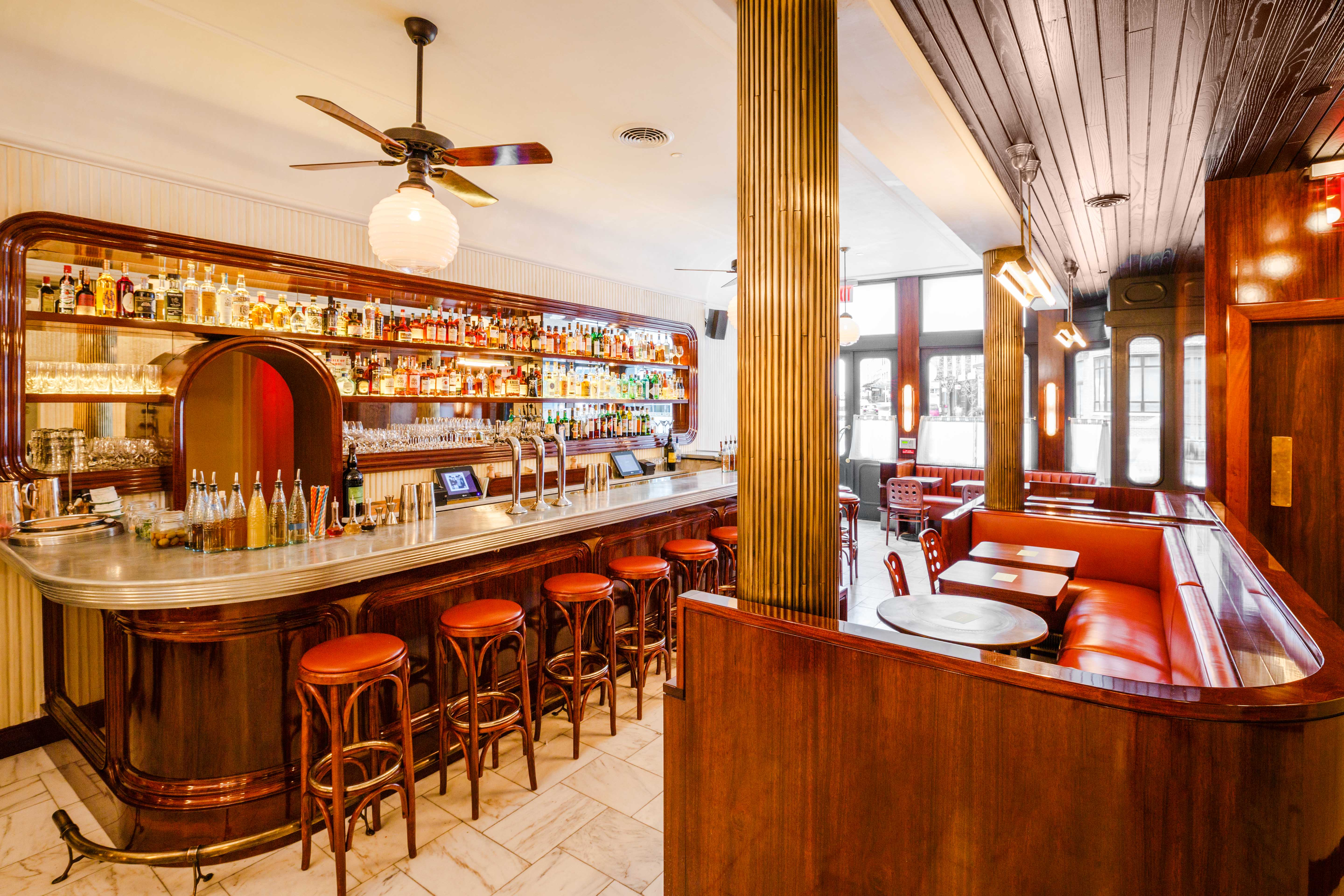 Frenchette's bar with red stools and red booths alongside