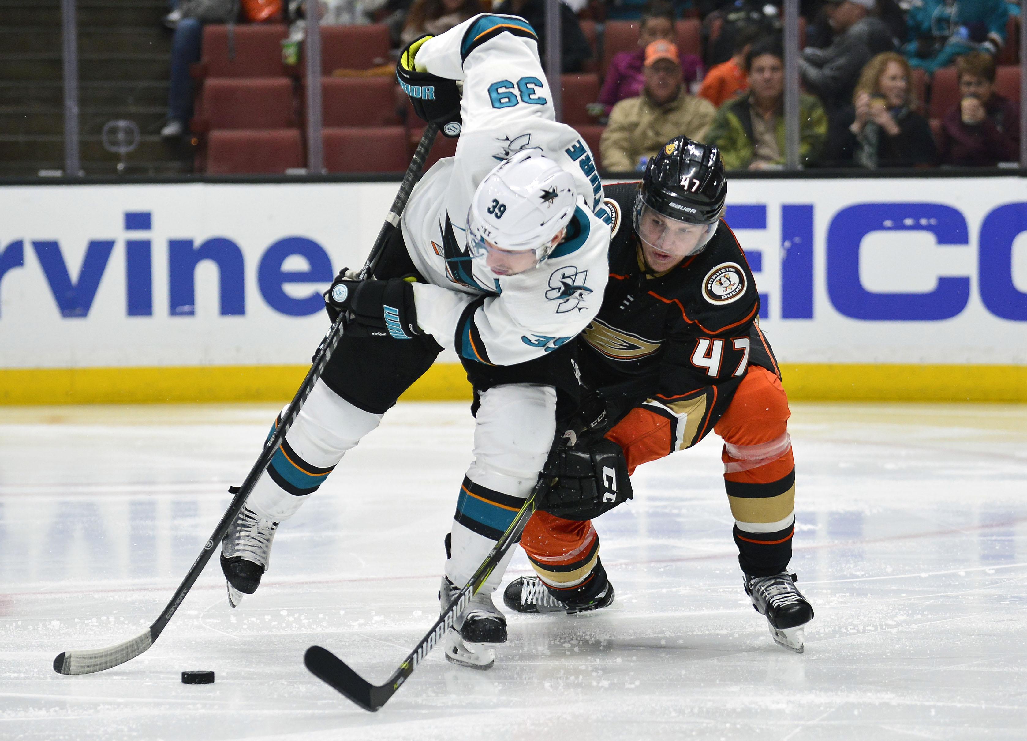 January 21, 2018; Anaheim, CA, USA; Anaheim Ducks defenseman Hampus Lindholm (47) plays for the puck against San Jose Sharks center Logan Couture (39) during the third period at Honda Center.