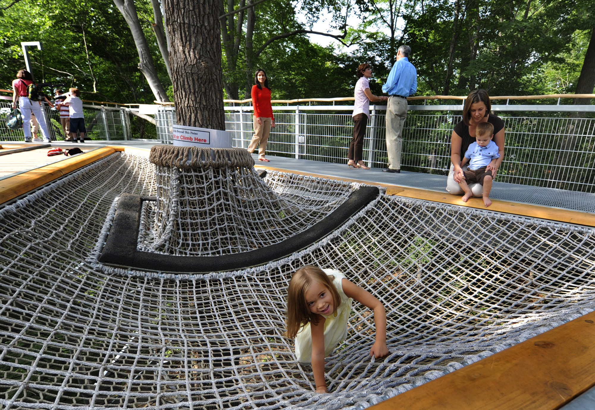 Children play in a playground in Philadelphia that has a net under a tree.
