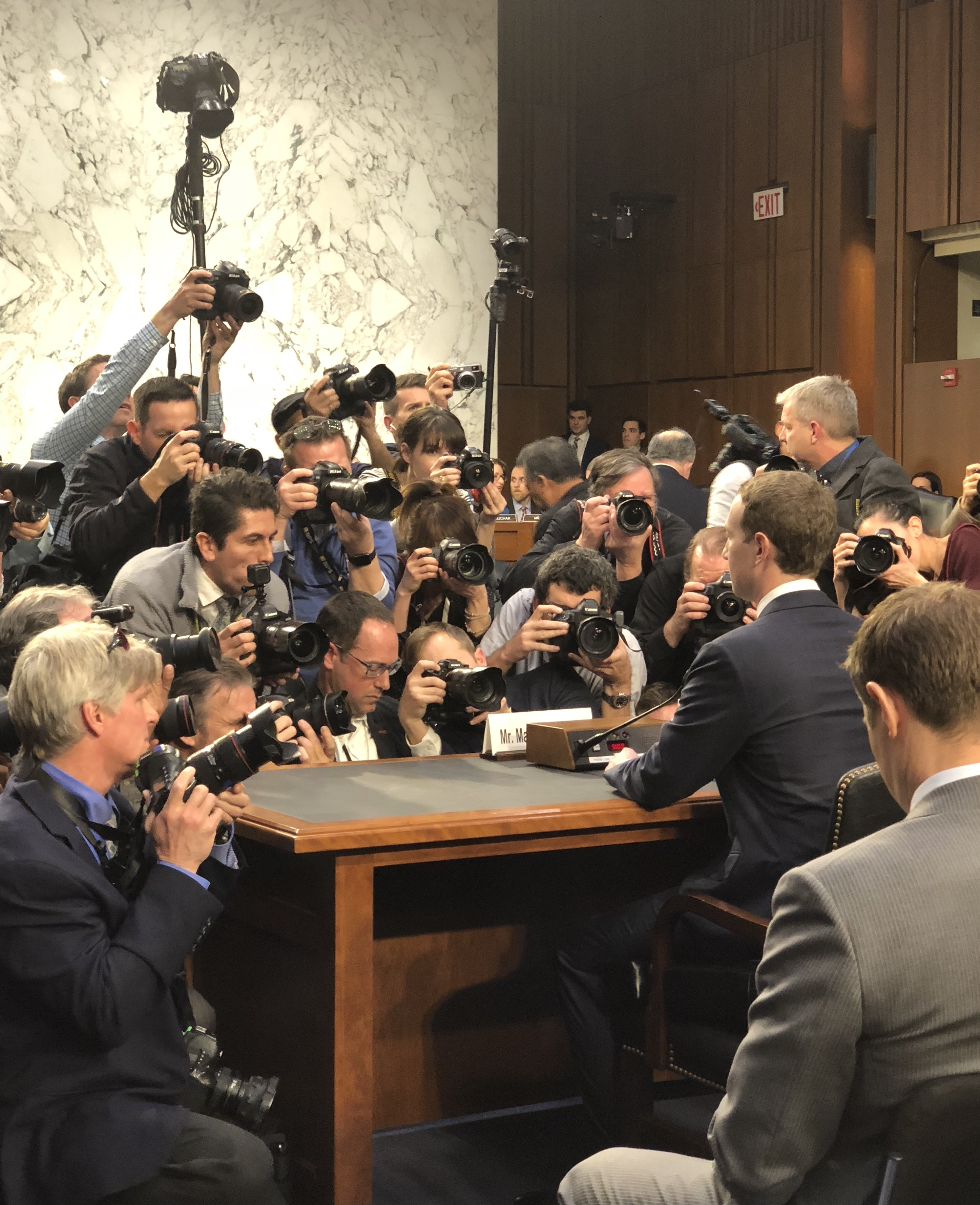 Facebook CEO Mark Zuckerberg, seated at the table where he will testify to Congress, surrounded by photographers