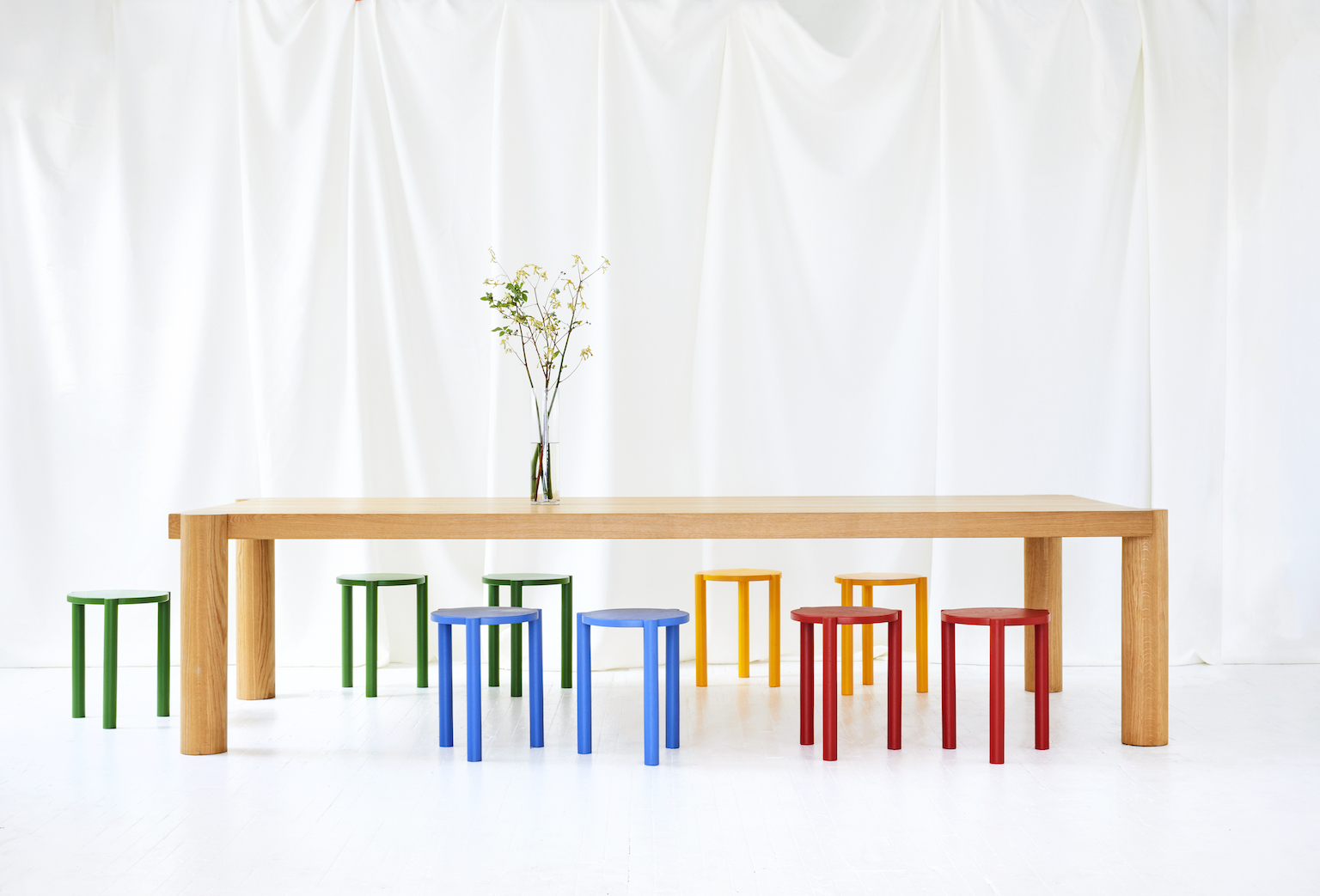 Large oak dining table with round legs surrounded by three-legged stools (also with round legs) in different colors against white backdrop.