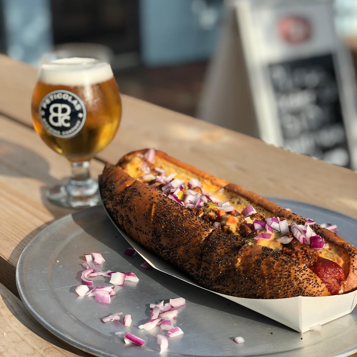 A hot dog on a pretzel bun topped with cheese and red onions. A chalice of light colored beer sits in the background.