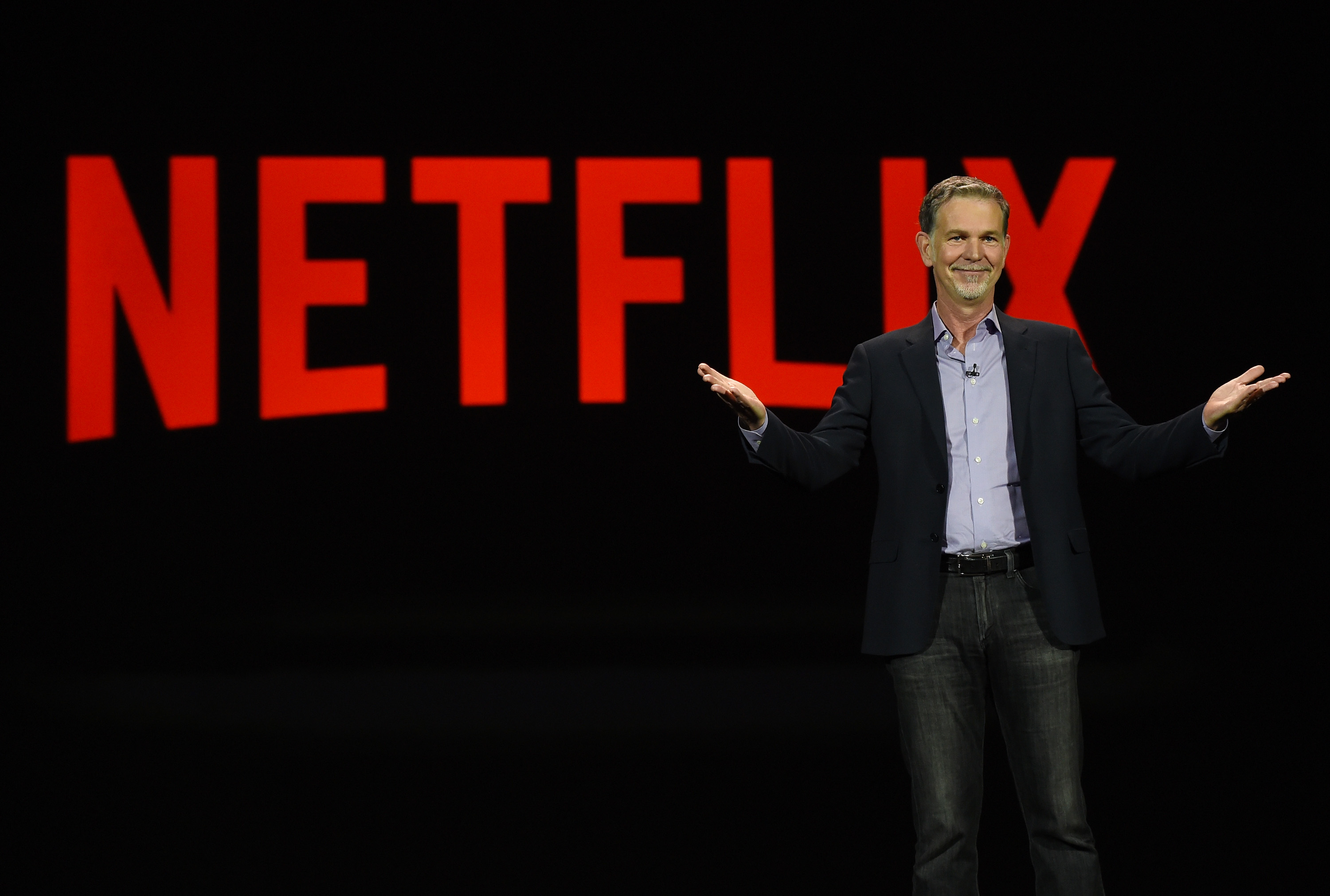 """Netflix CEO Reed Hastingsstands in front of a sign that reads """"Netflix."""""""