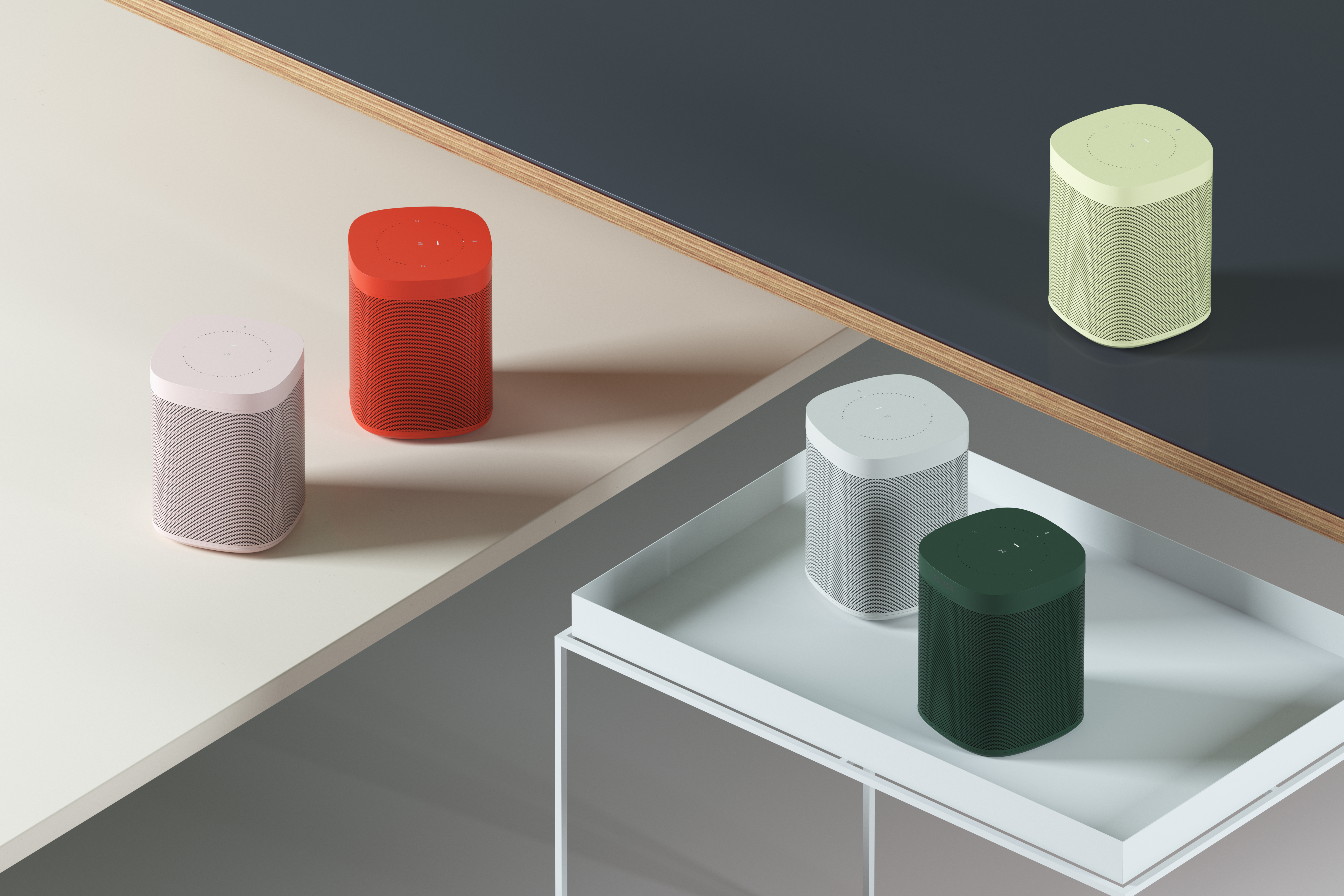 A cluster of five rectangular volumes with rounded edges in different colors displayed on two table tops.