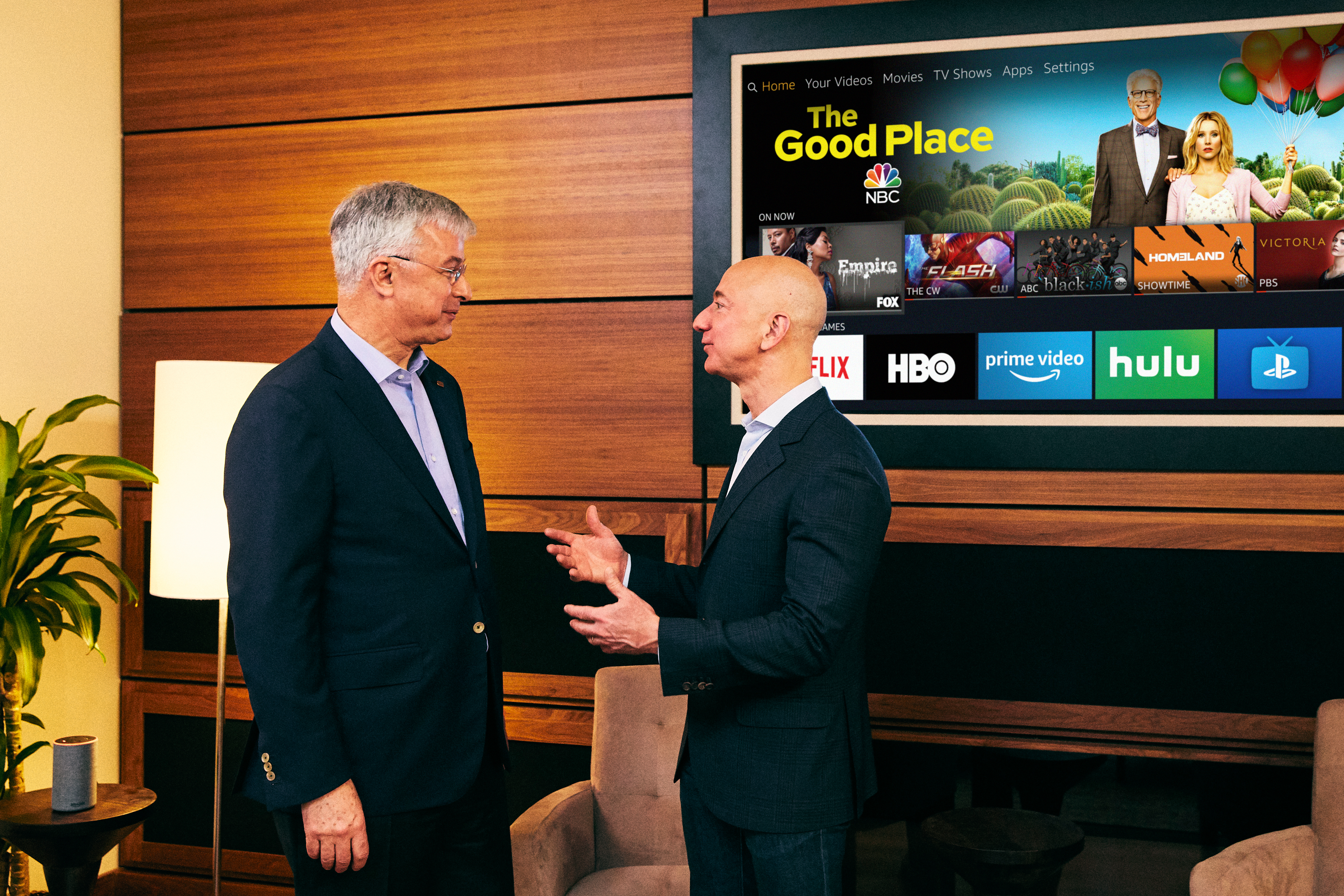 Amazon CEO Jeff Bezos chats with Best Buy CEO Hubert Joly in front of a Fire TV screen
