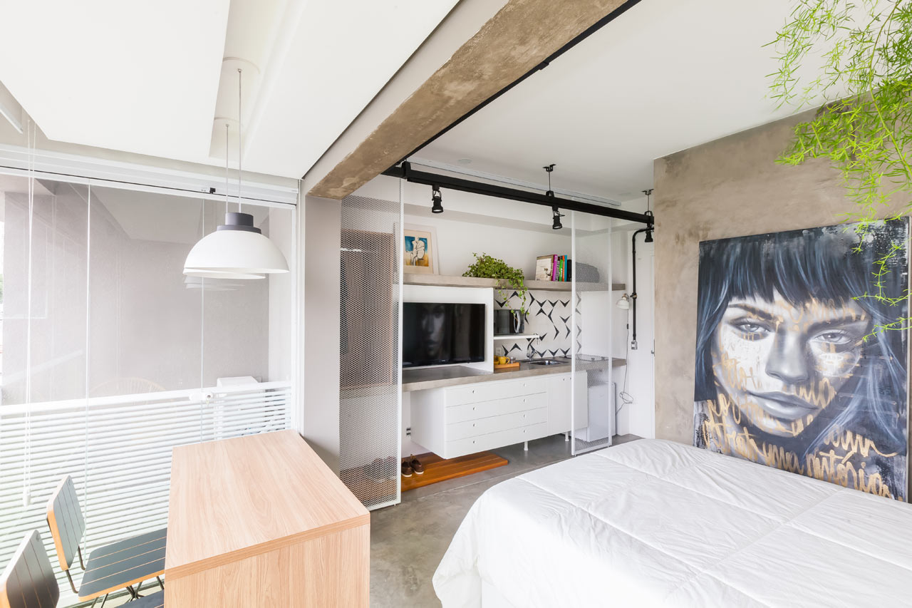 Small studio apartment with white walls with concrete accents, bed, desk, and small kitchen counter.