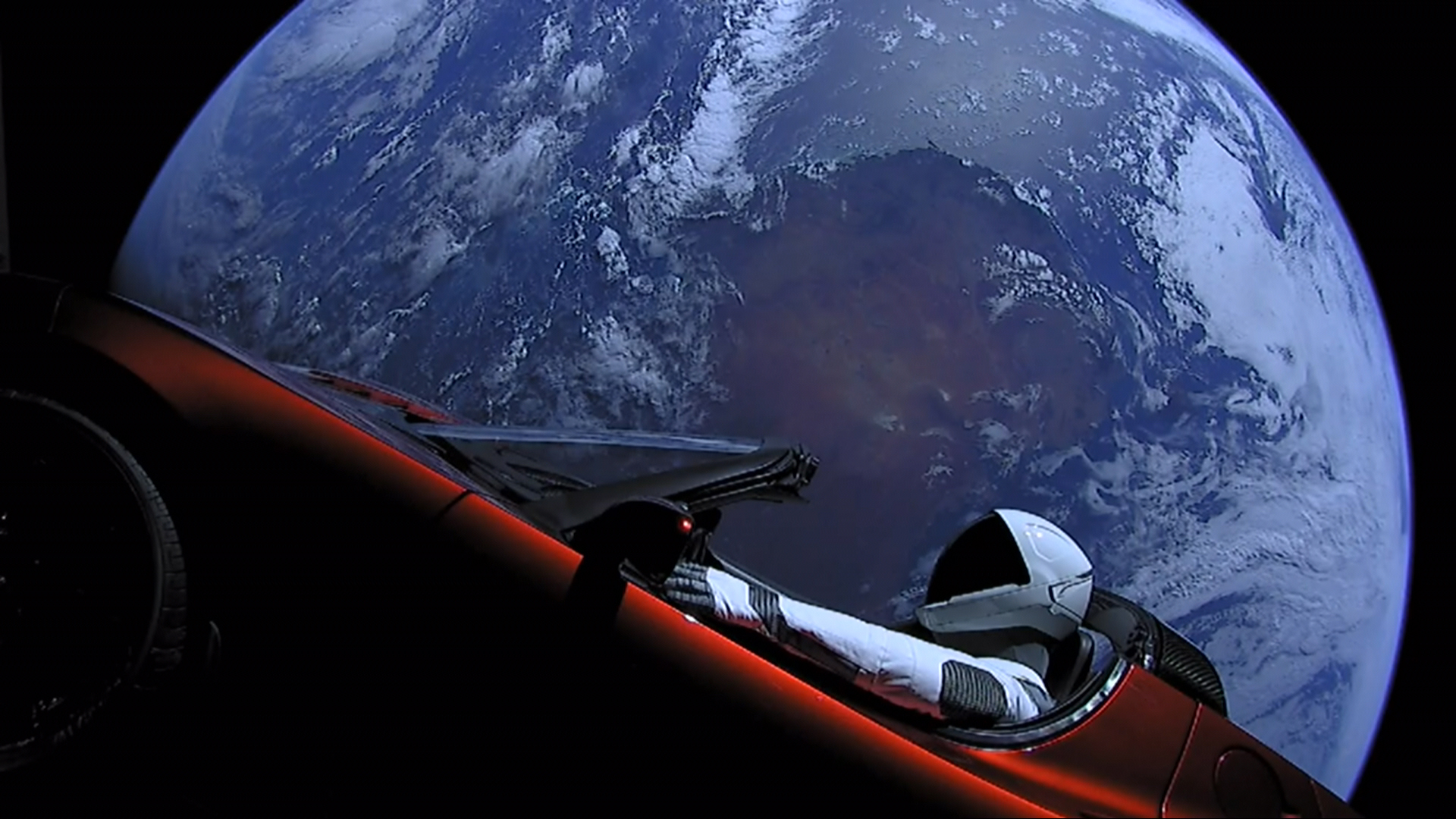 A Tesla roadster with an astronaut dummy driving it, with Earth in the background