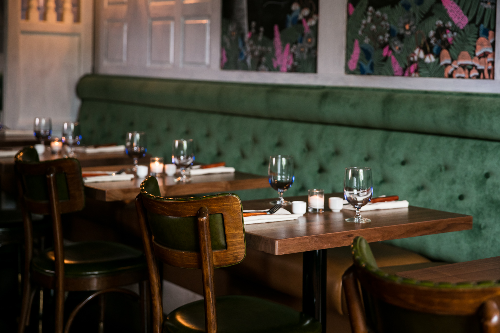 Green fabric upholstered booths next to a wood table with wood chairs and table settings at Lady of the House.