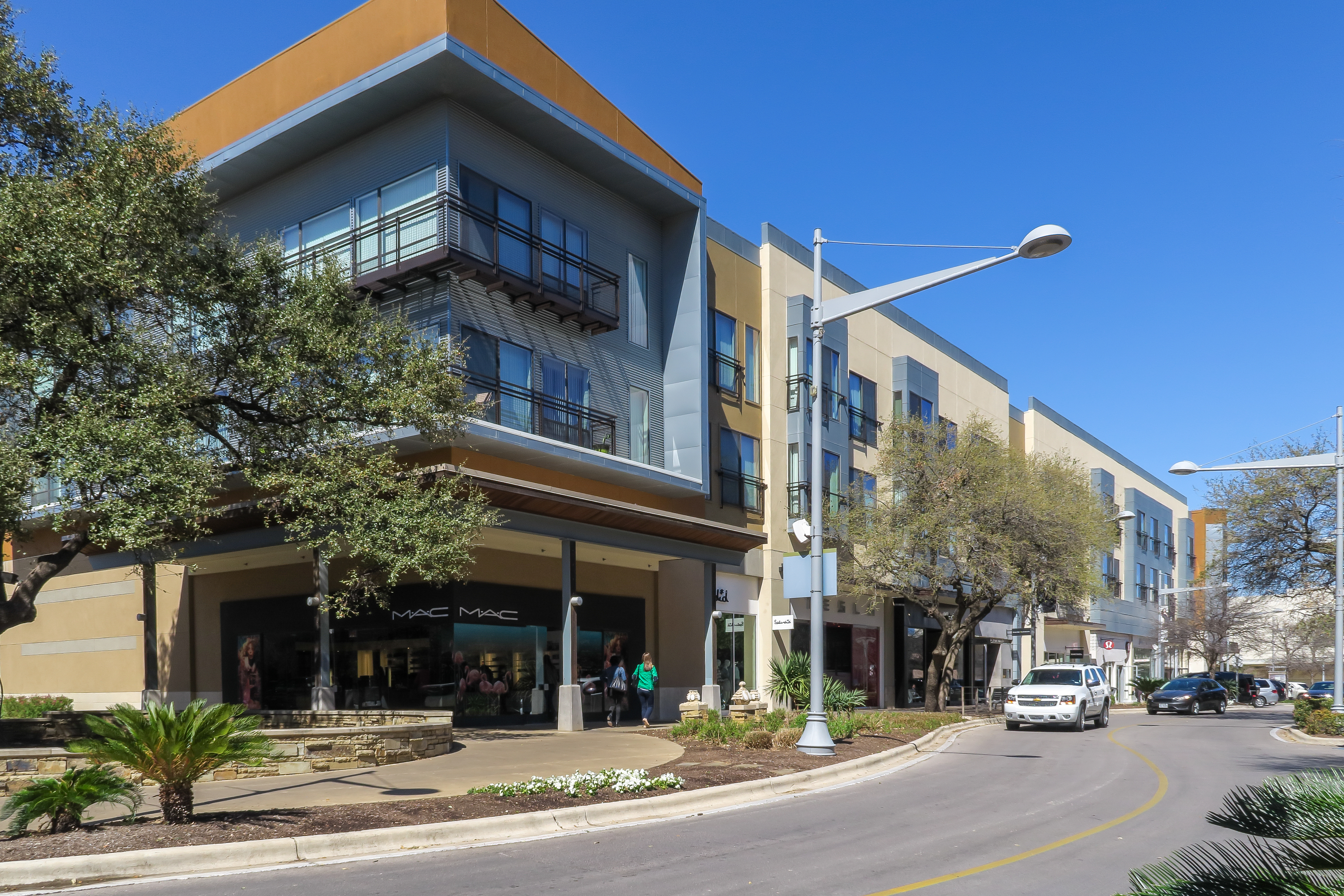A block-long, two-story contemporary building on a curved street, part of a mixed-use development