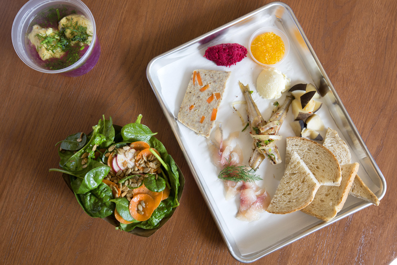 A platter of deli food, a soup, and a salad at Larder