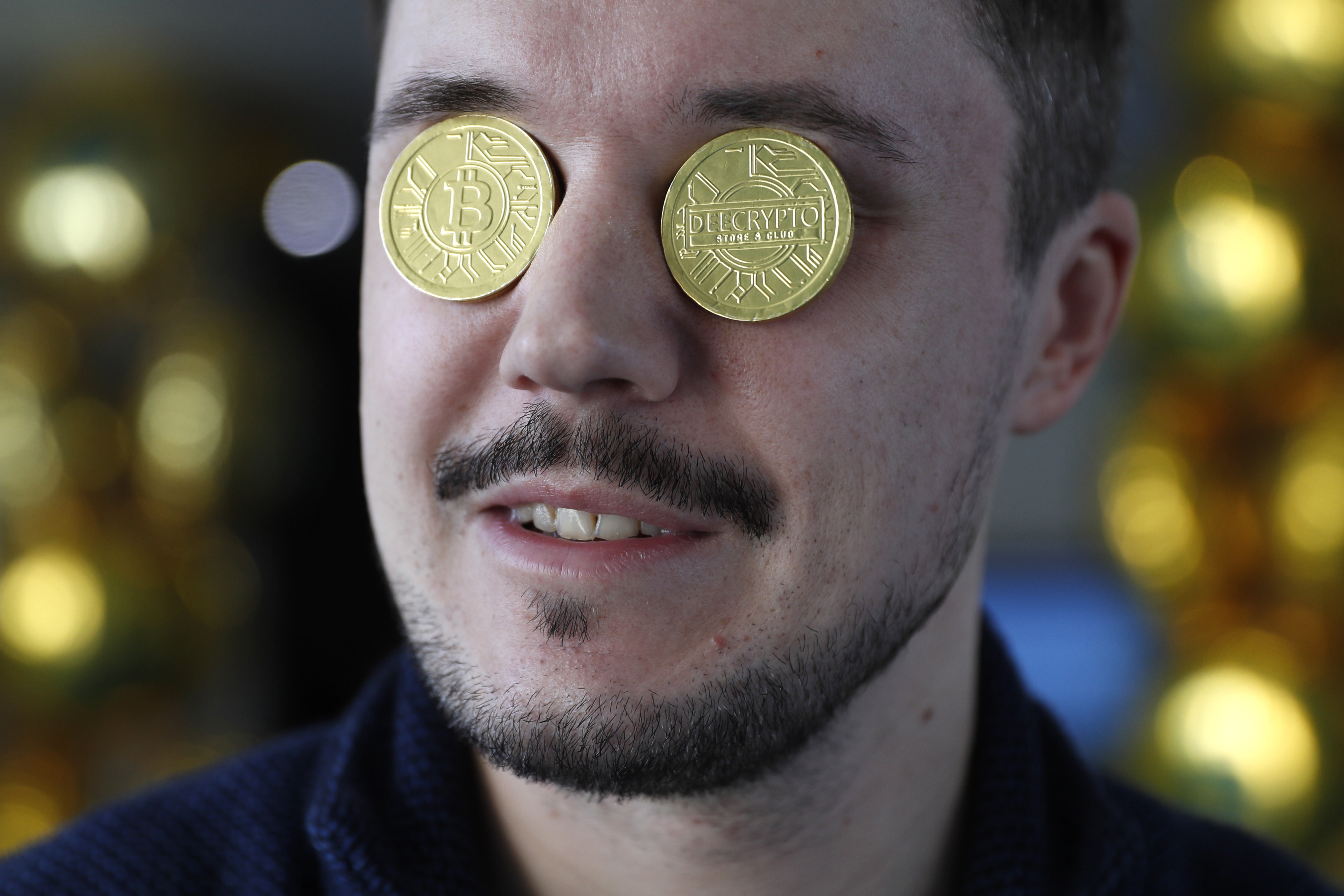 A man's face with gold coins representing bitcoins over his eyes.