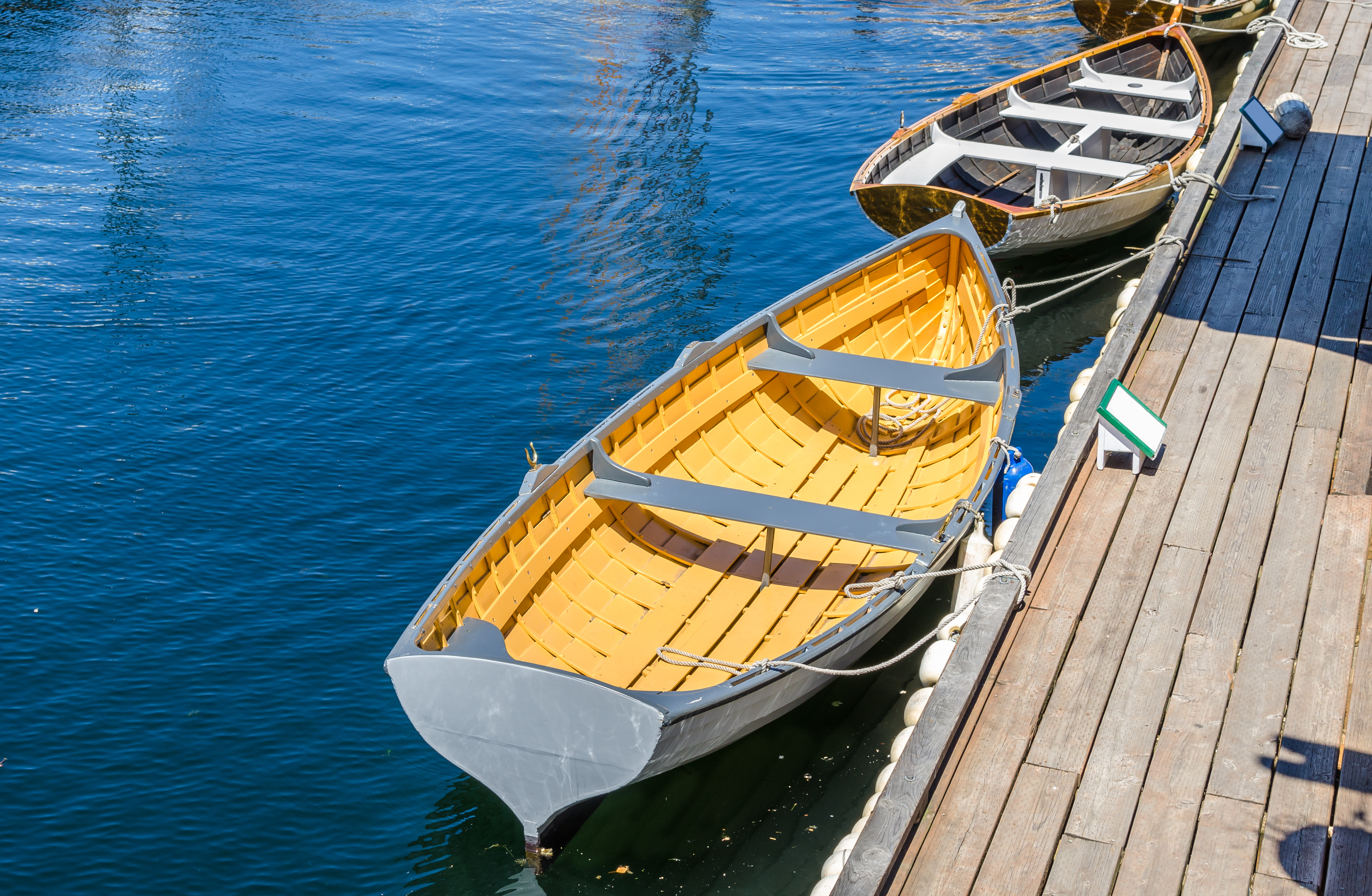 Two boats on a body of water next to a wooden pier. The boat in the foreground has a yellow interior.