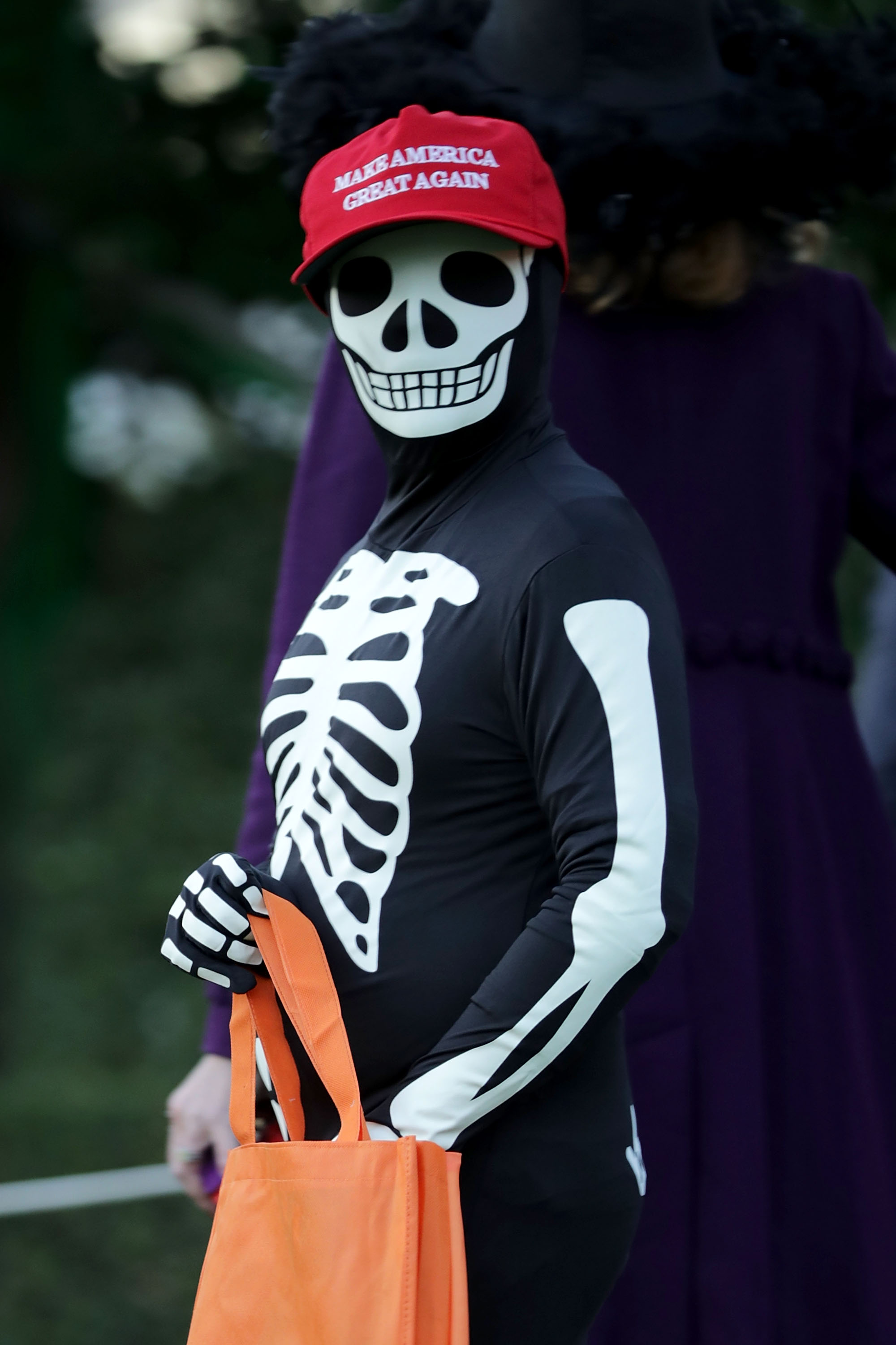 A person in a skeleton costume wearing a MAGA hat