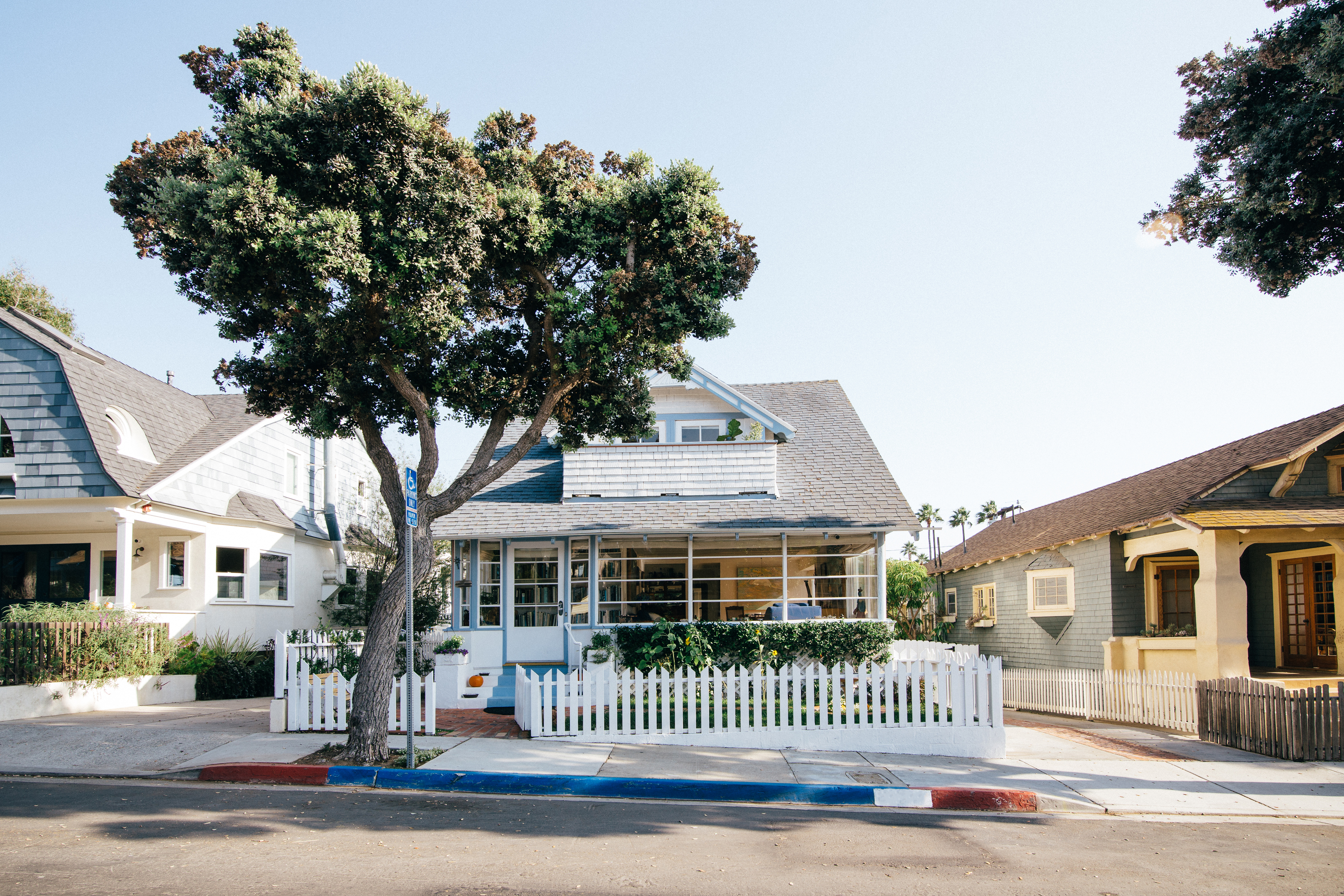 Pretty bungalow home, with a house on each side. Large tree in front. The home is white, with light blue trim, lots of windows, green in the front yard with a white picket fence.