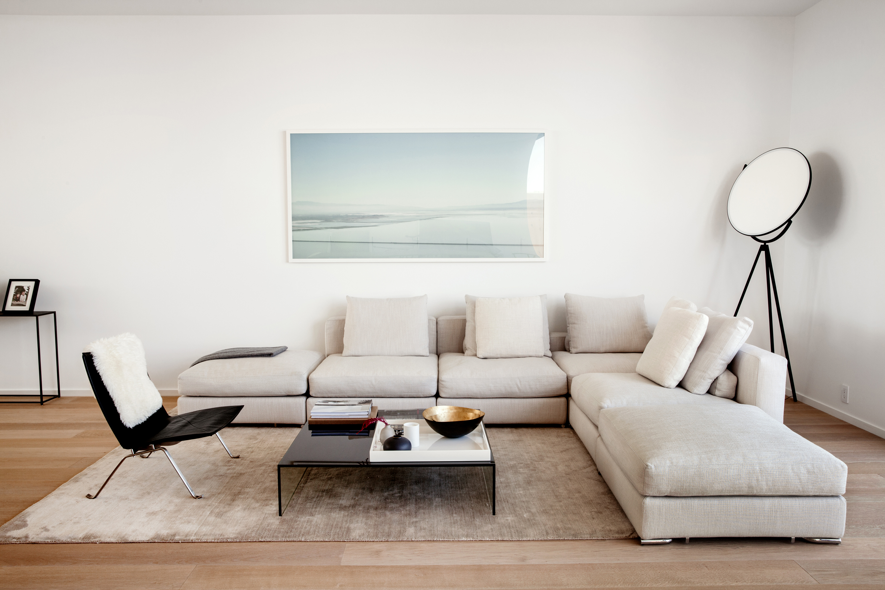 A brightly lit living room with a light beige sectional, black accent chair, and light blue framed landscape painting.