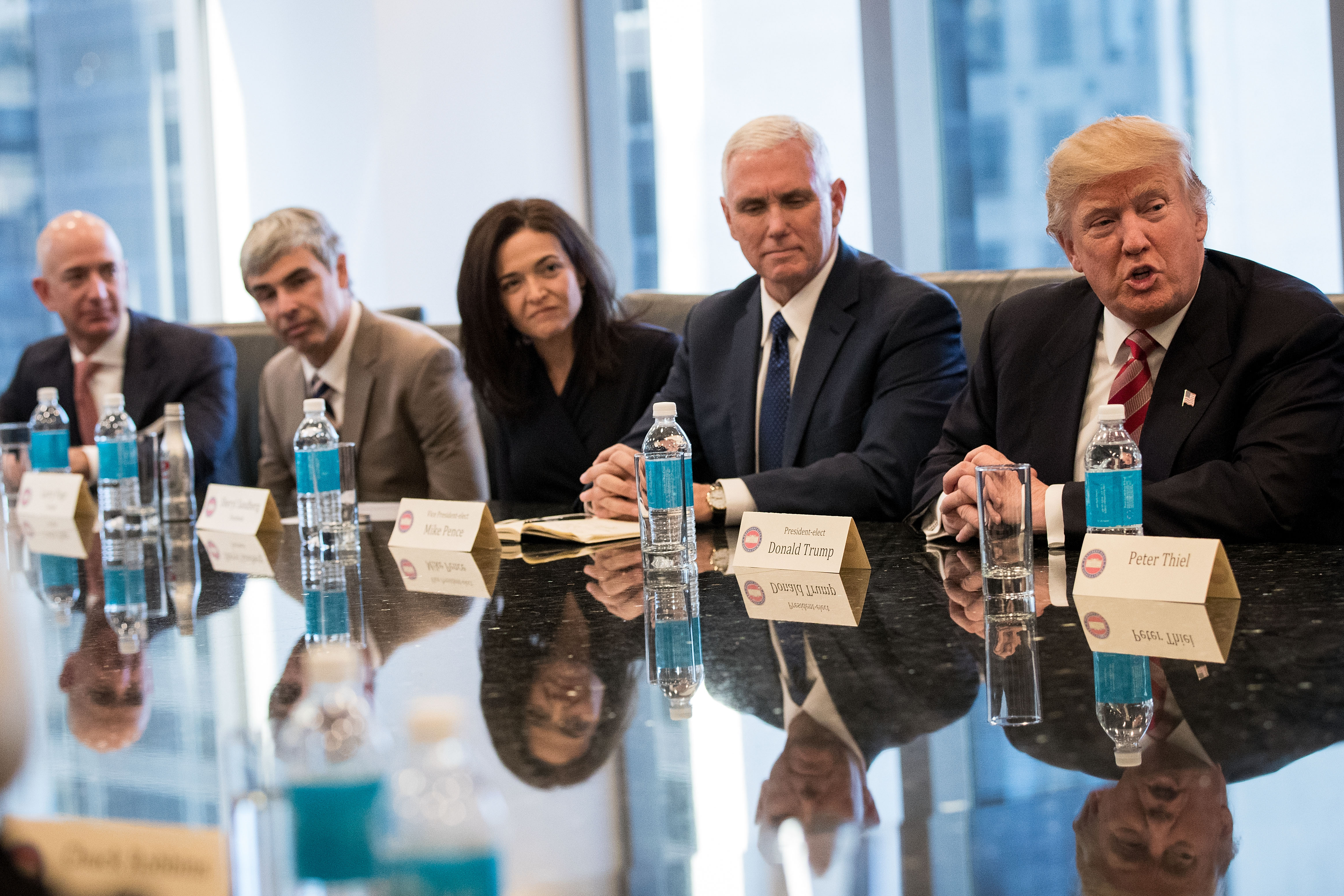 Amazon CEO Jeff Bezos, Alphabet CEO Larry Page, Facebook COO Sheryl Sandberg, VP Mike Pence and President Donald Trump sit at a conference table