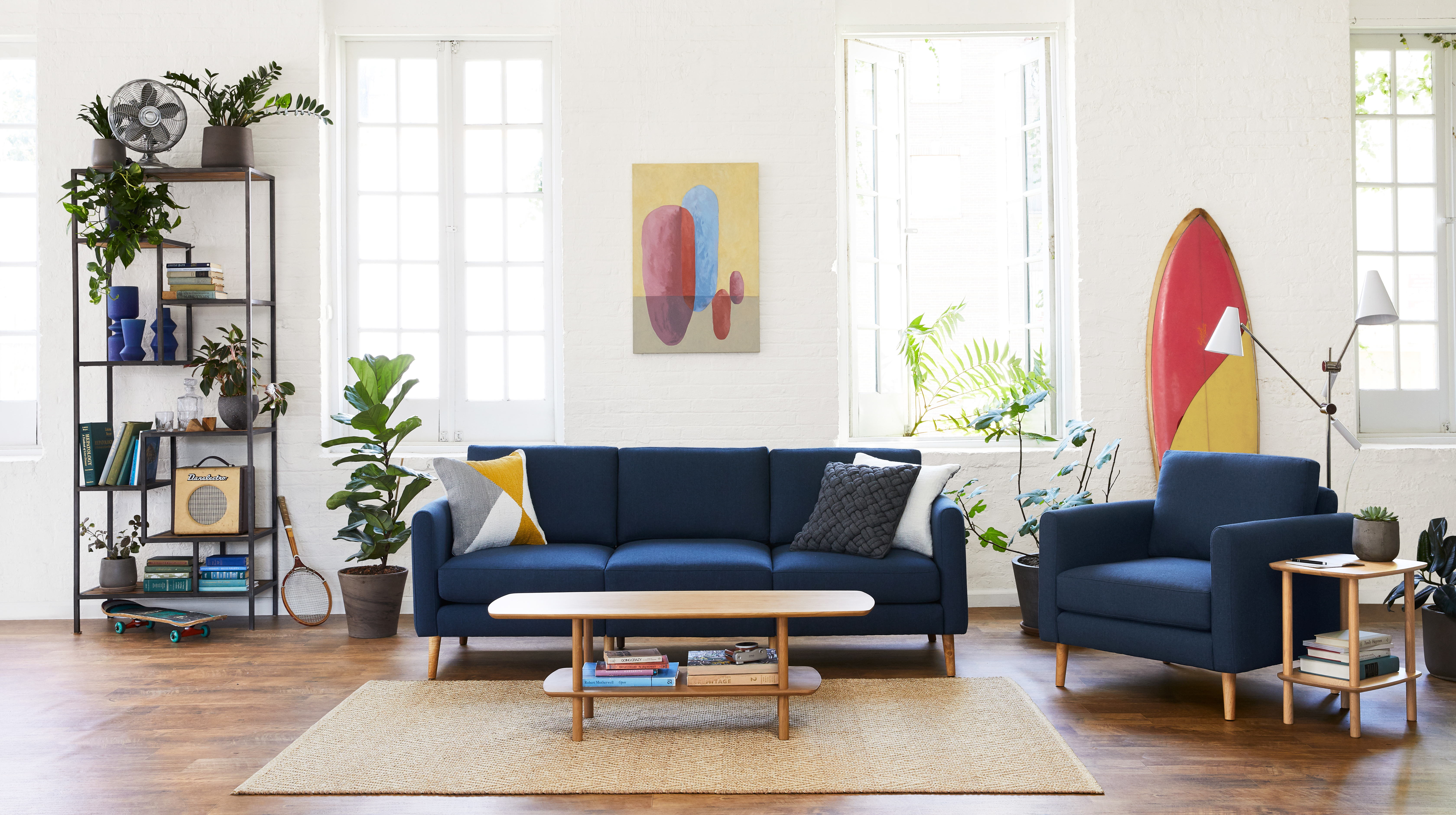 A living room with navy blue sofa and armchair. There is a wooden coffee table and tan rug.