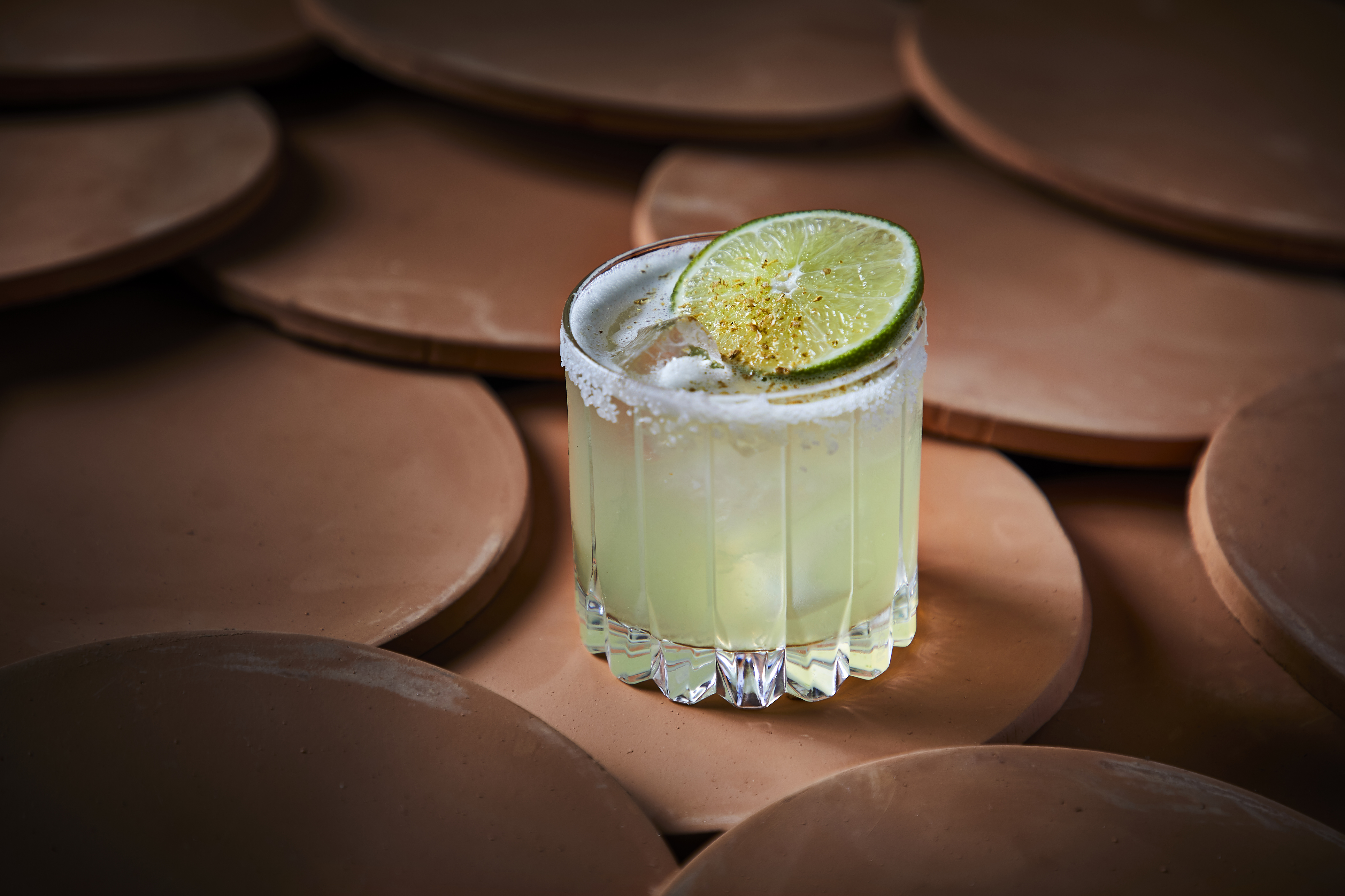 A margarita in a high ball glass with a wedge of lime.