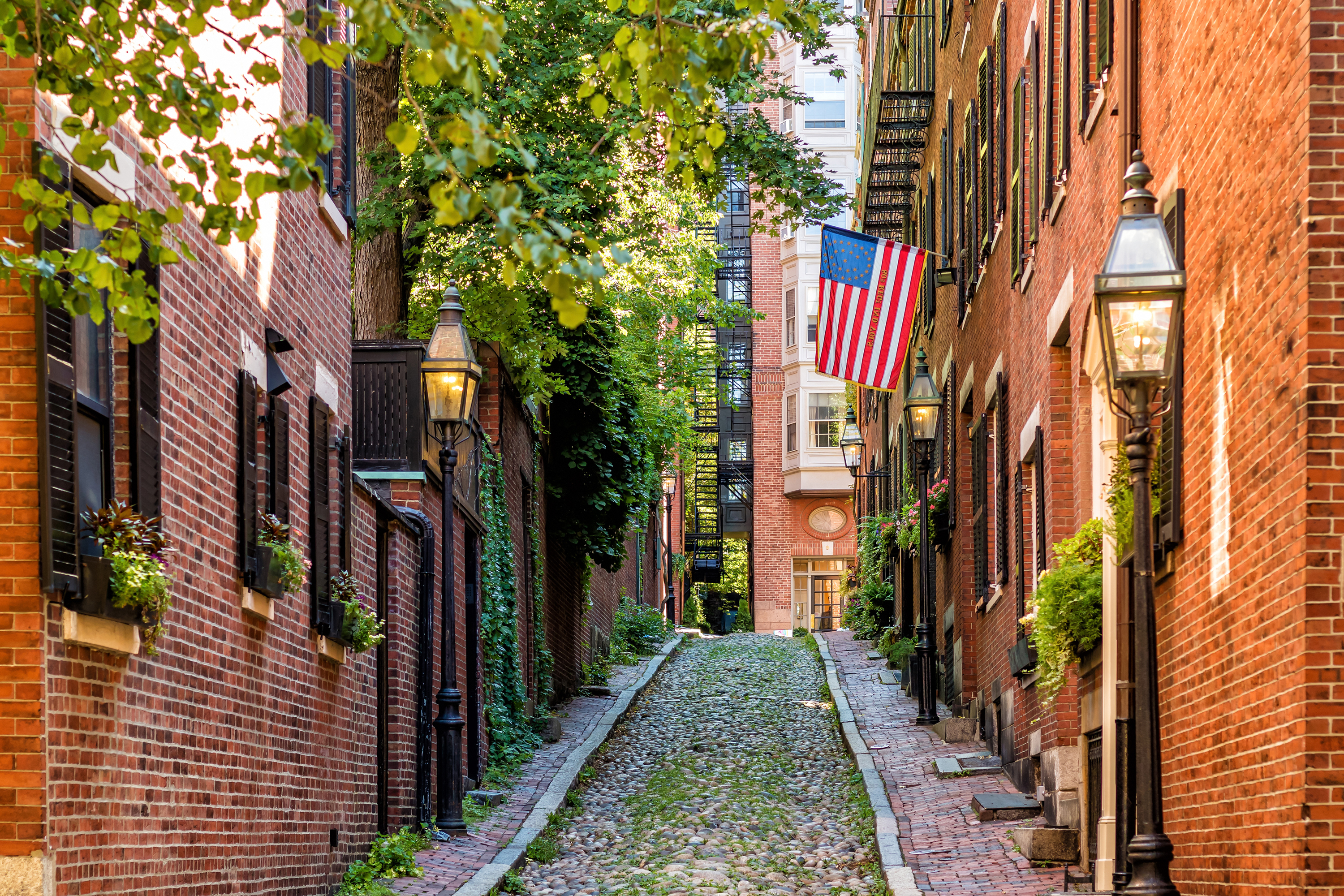 A narrow cobblestone street going uphill and there are townhouses on either side.