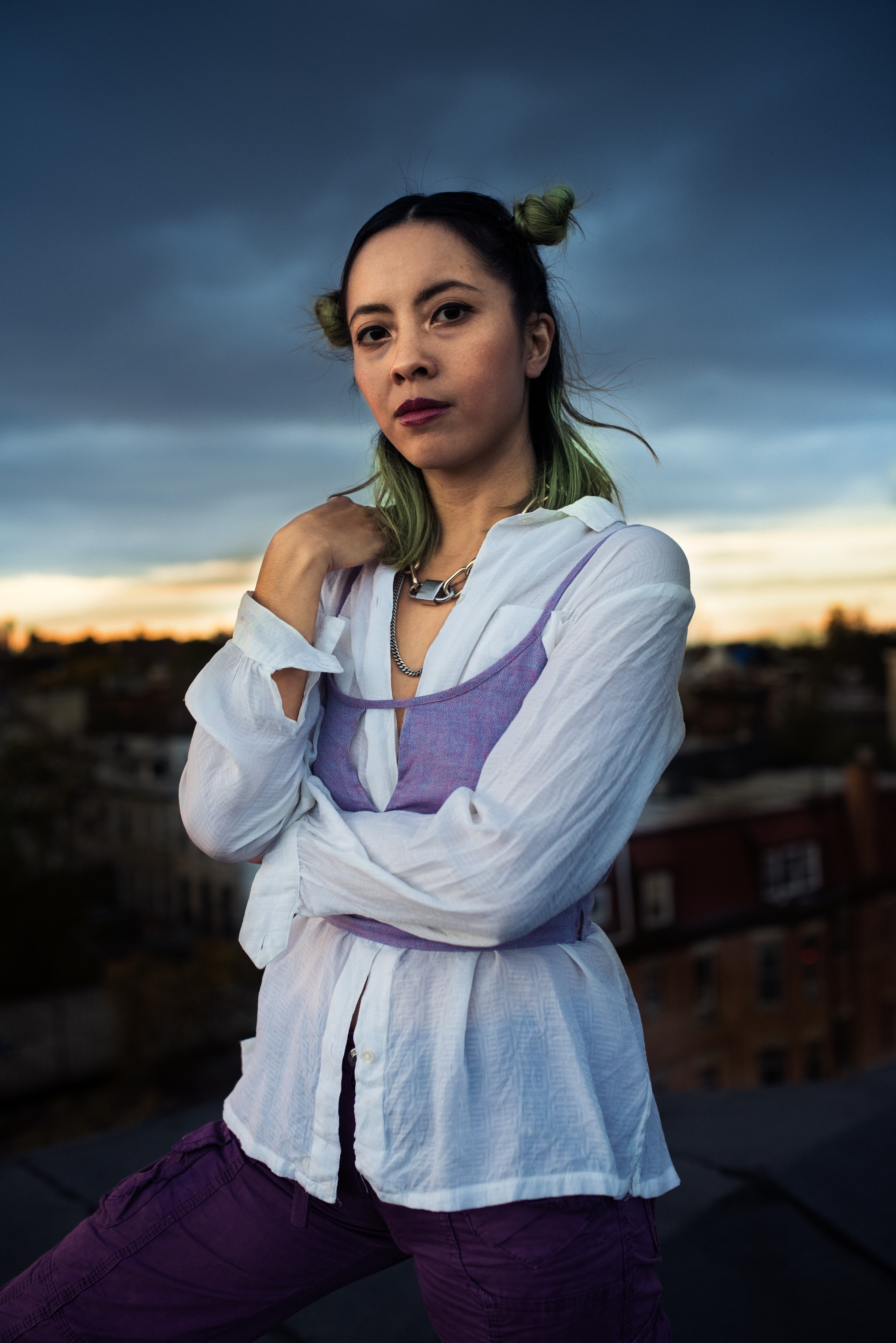 A woman with a white button-down shirt layered under a purple cropped camisole stands and looks directly at the camera