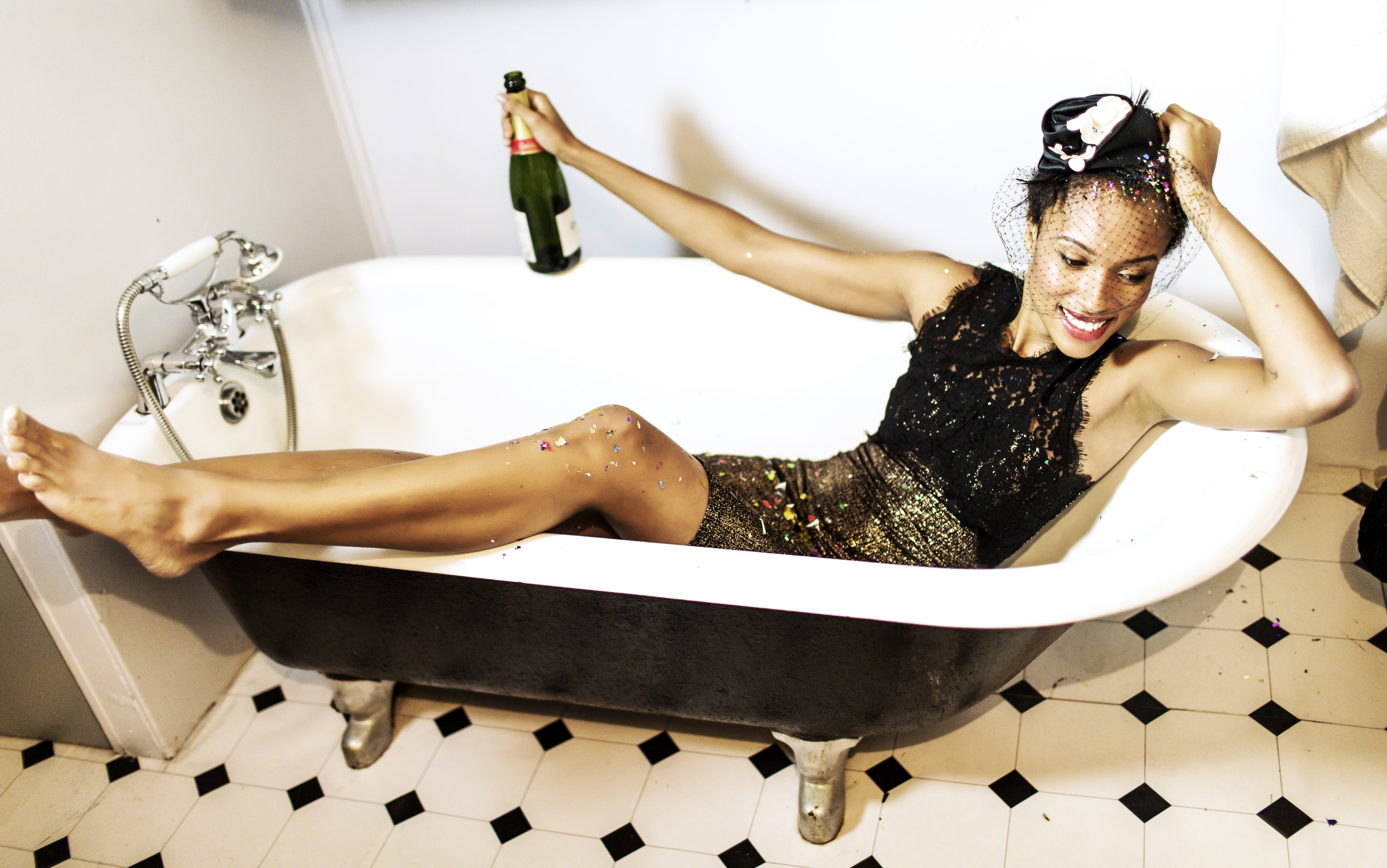 A woman in a little black dress holds a bottle of champagne while lying in an empty bath tub.