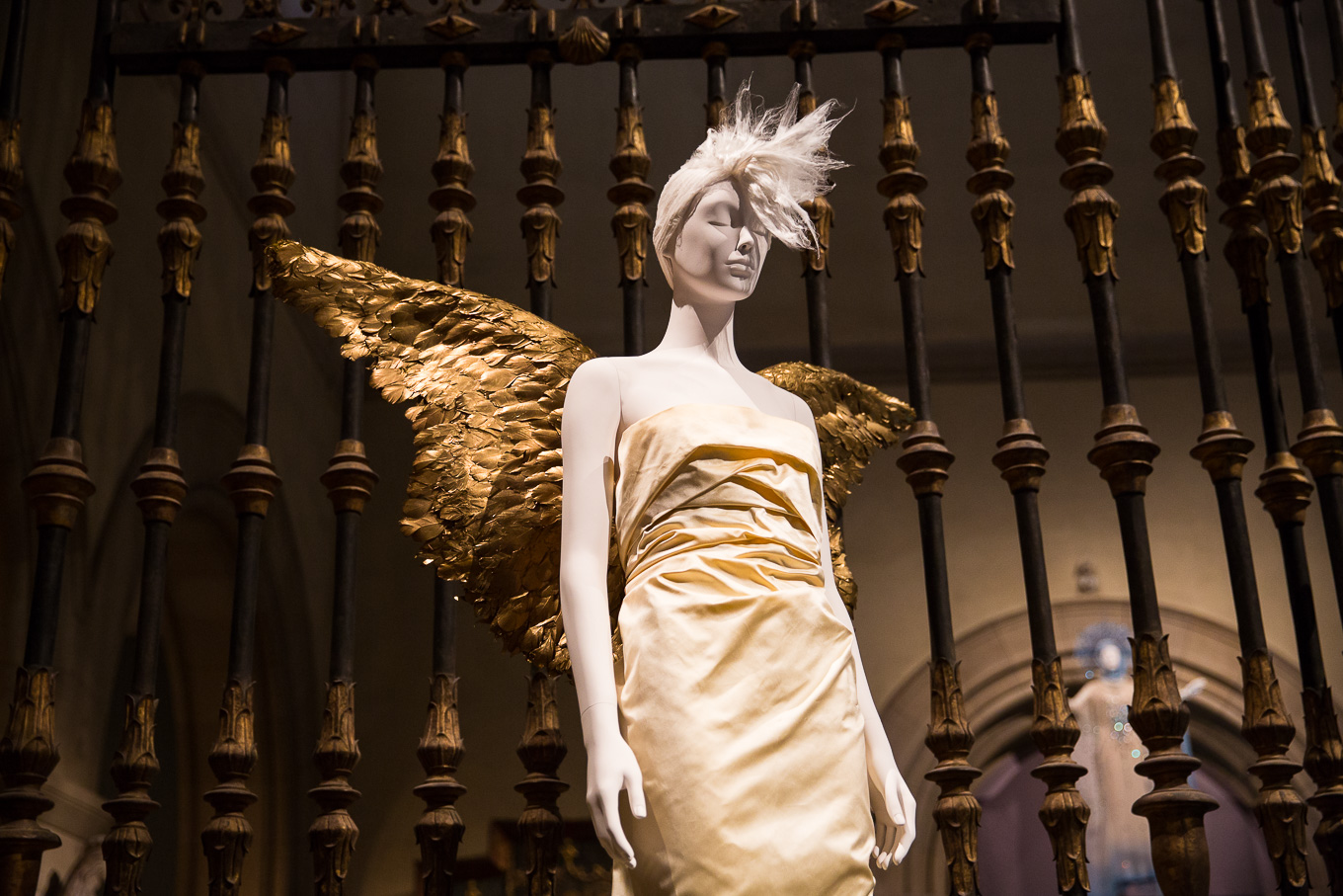 A mannequin wears an ivory evening dress and gold angel wings.