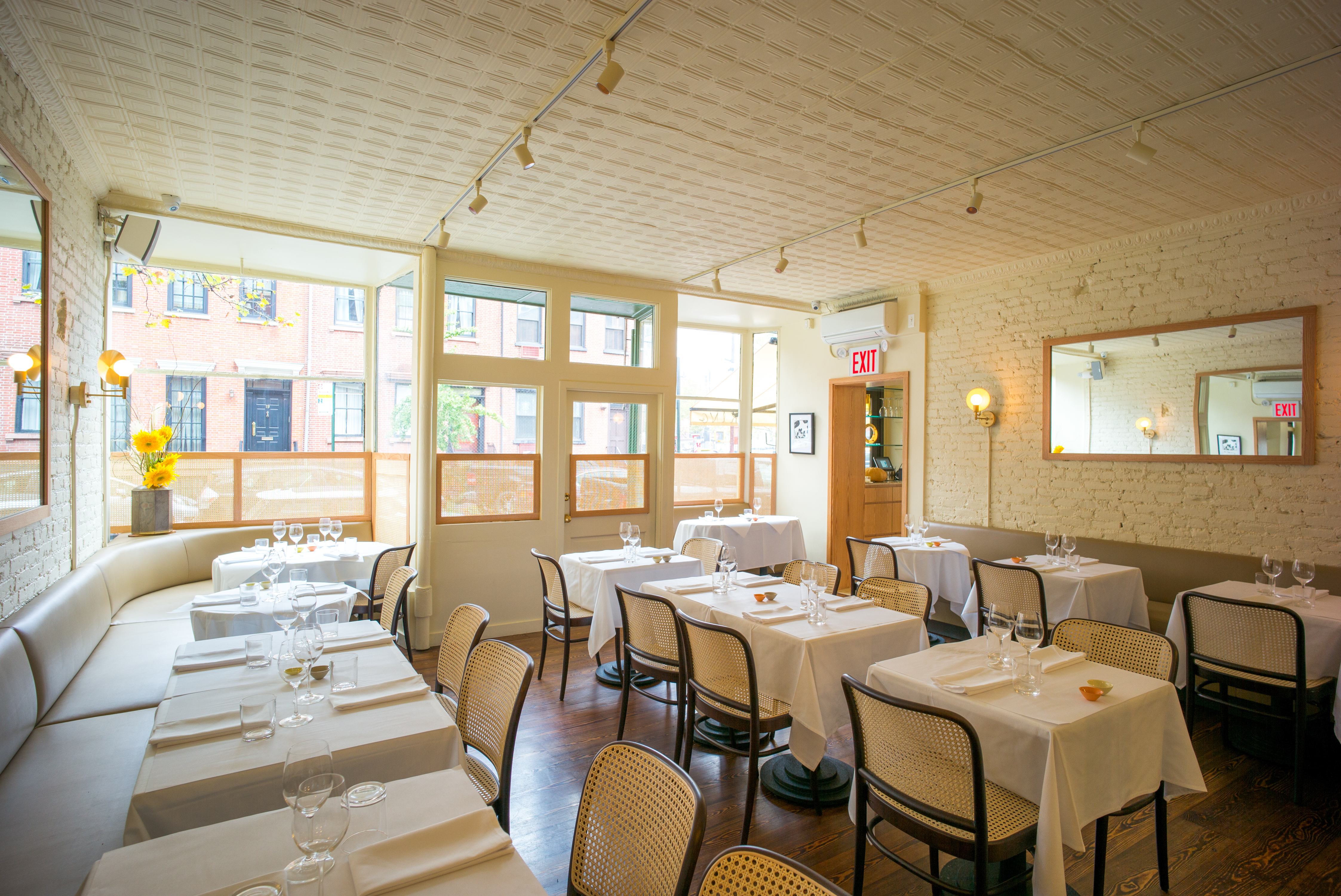 A sunny dining room with white tablecloth tables