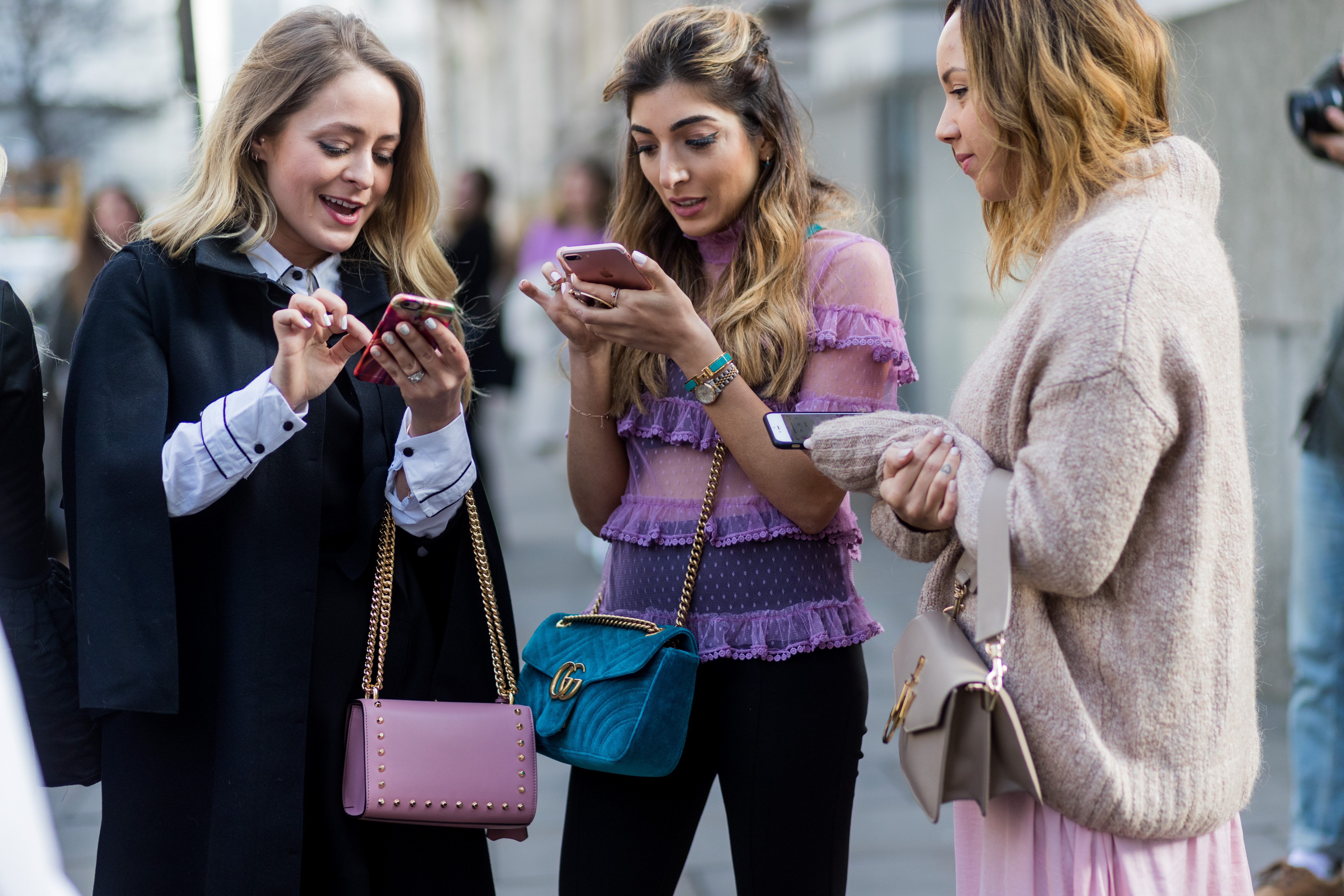 Three women stand on a street in London, interacting with their phones