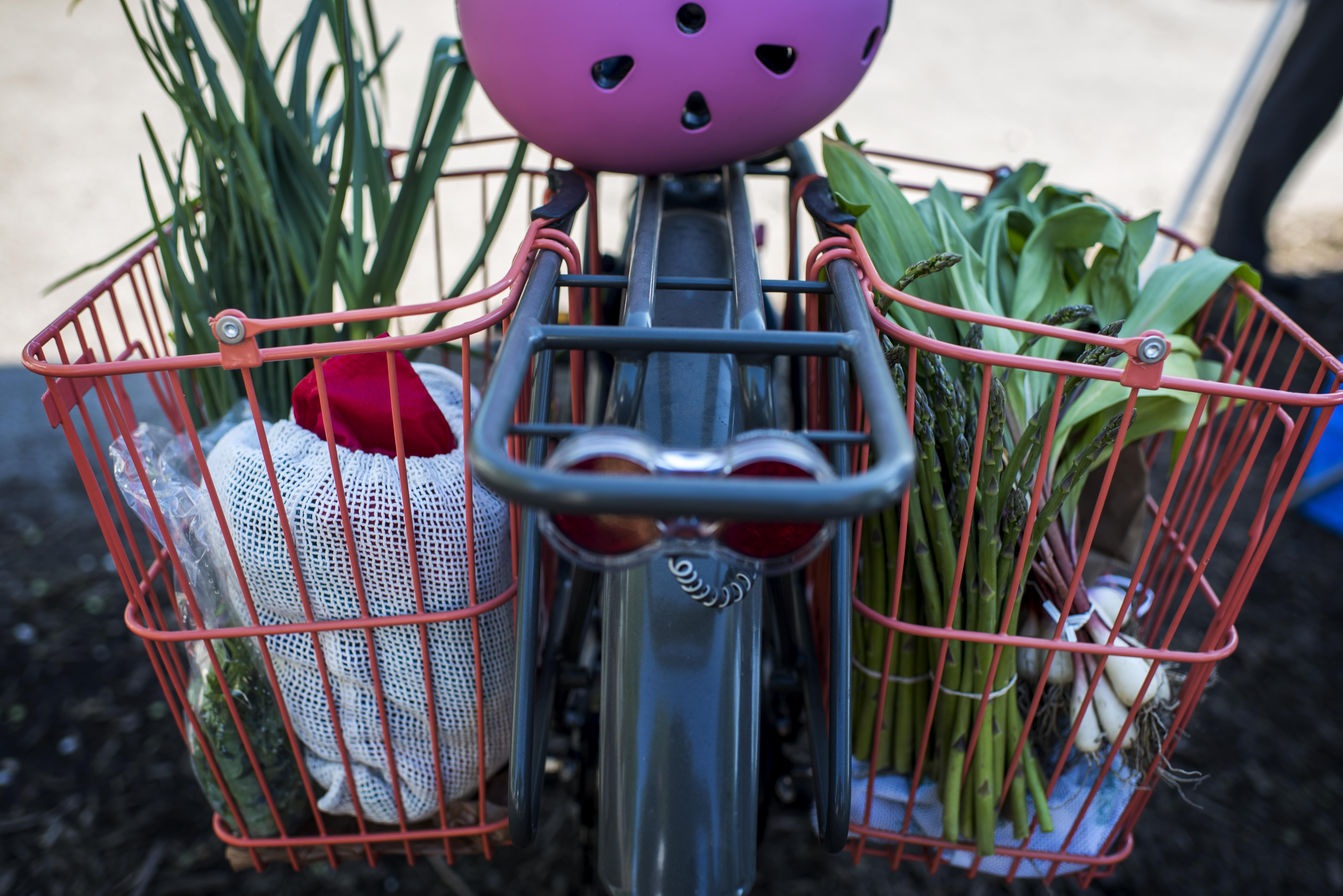 A blue bicycle with two red baskets secured to it. In the red baskets are various market items like produce. There is a pink helmet laying on top of the bicycle.