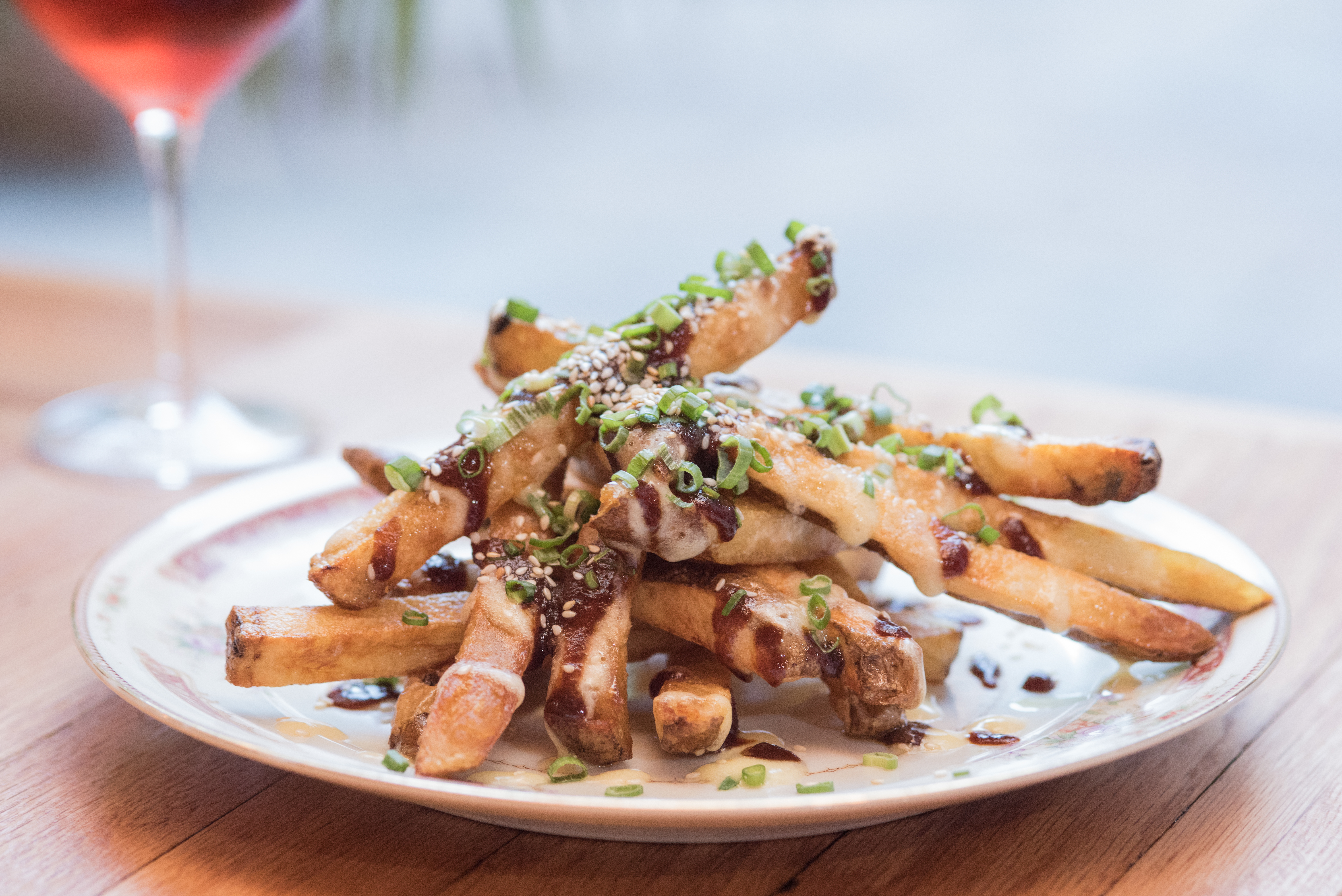 A plate of fries with scallions and sauce.