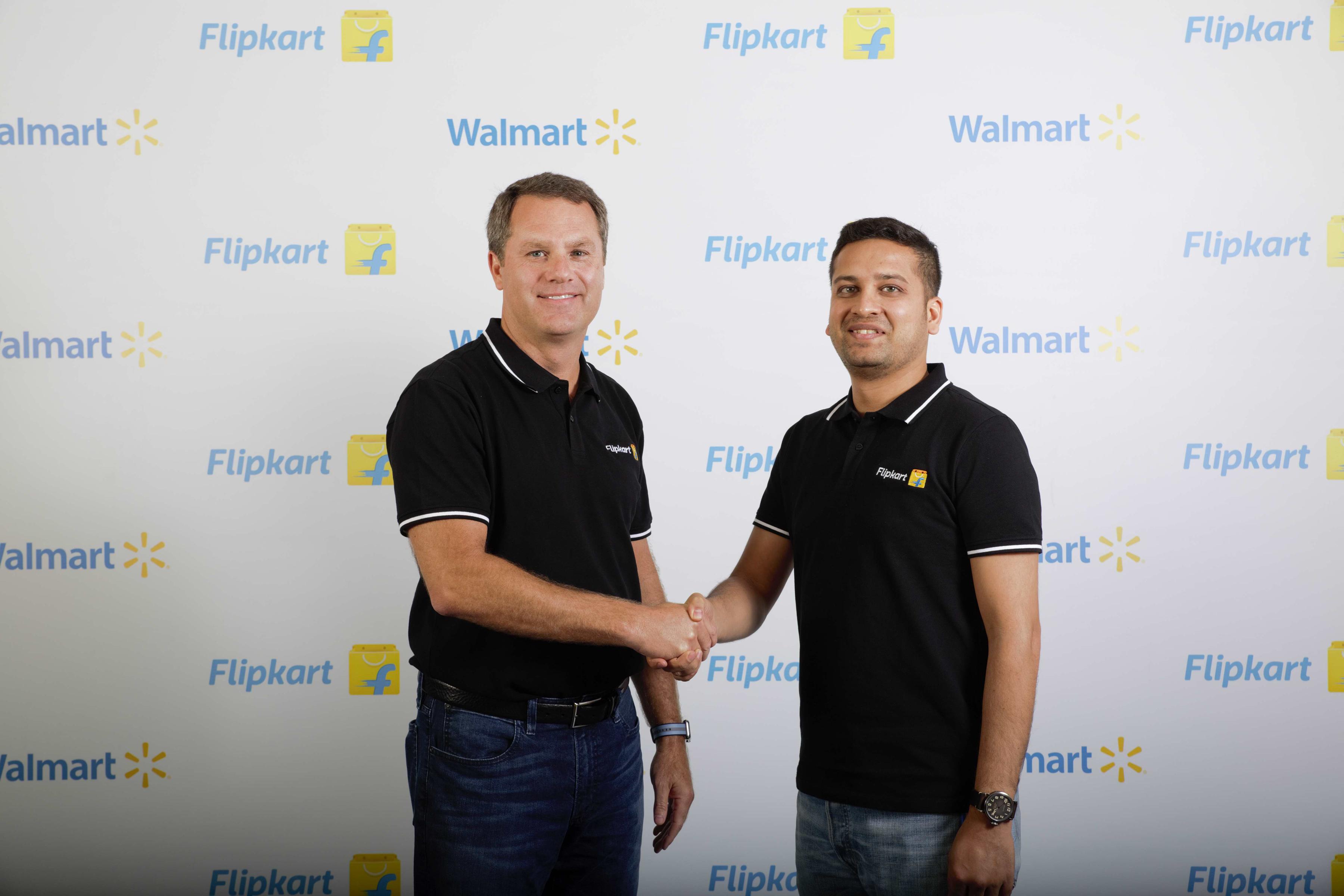 Walmart CEO Doug McMillon shakes hands and poses with Flipkart co-founder Binny Bansal