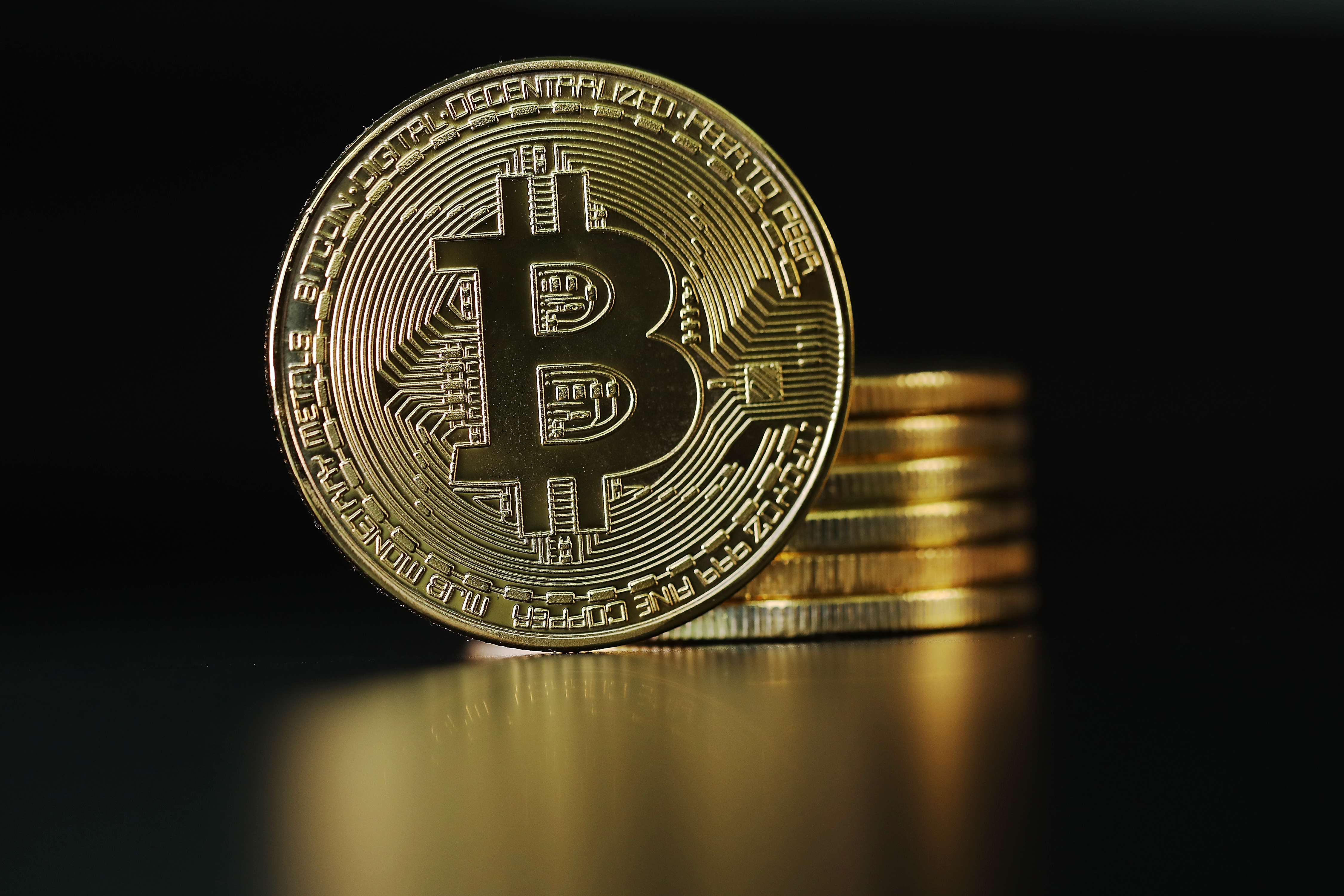 """A bitcoin cryptocurrency """"coin"""" in front of a stack of coins"""