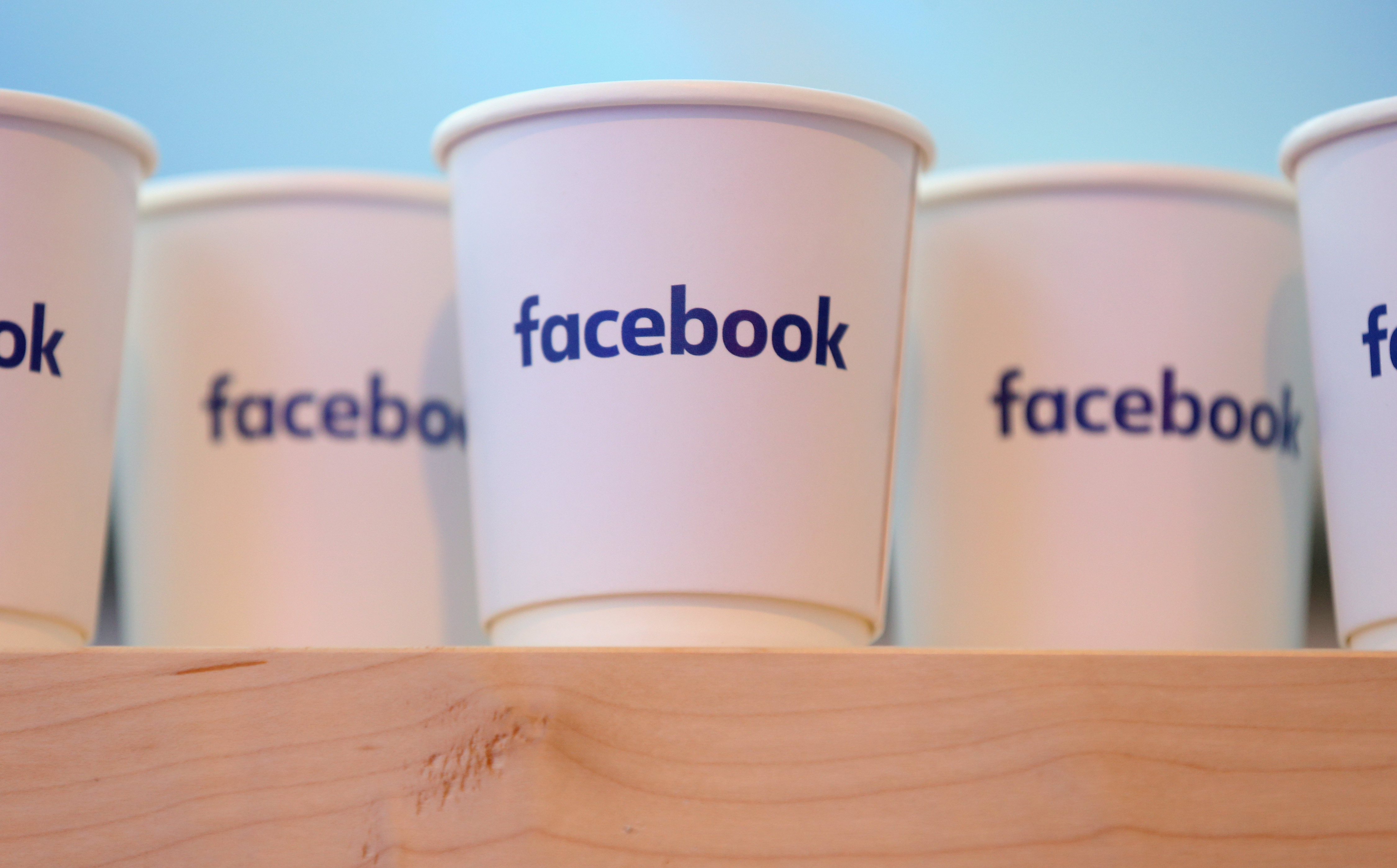 Facebook logo on white paper coffee cups