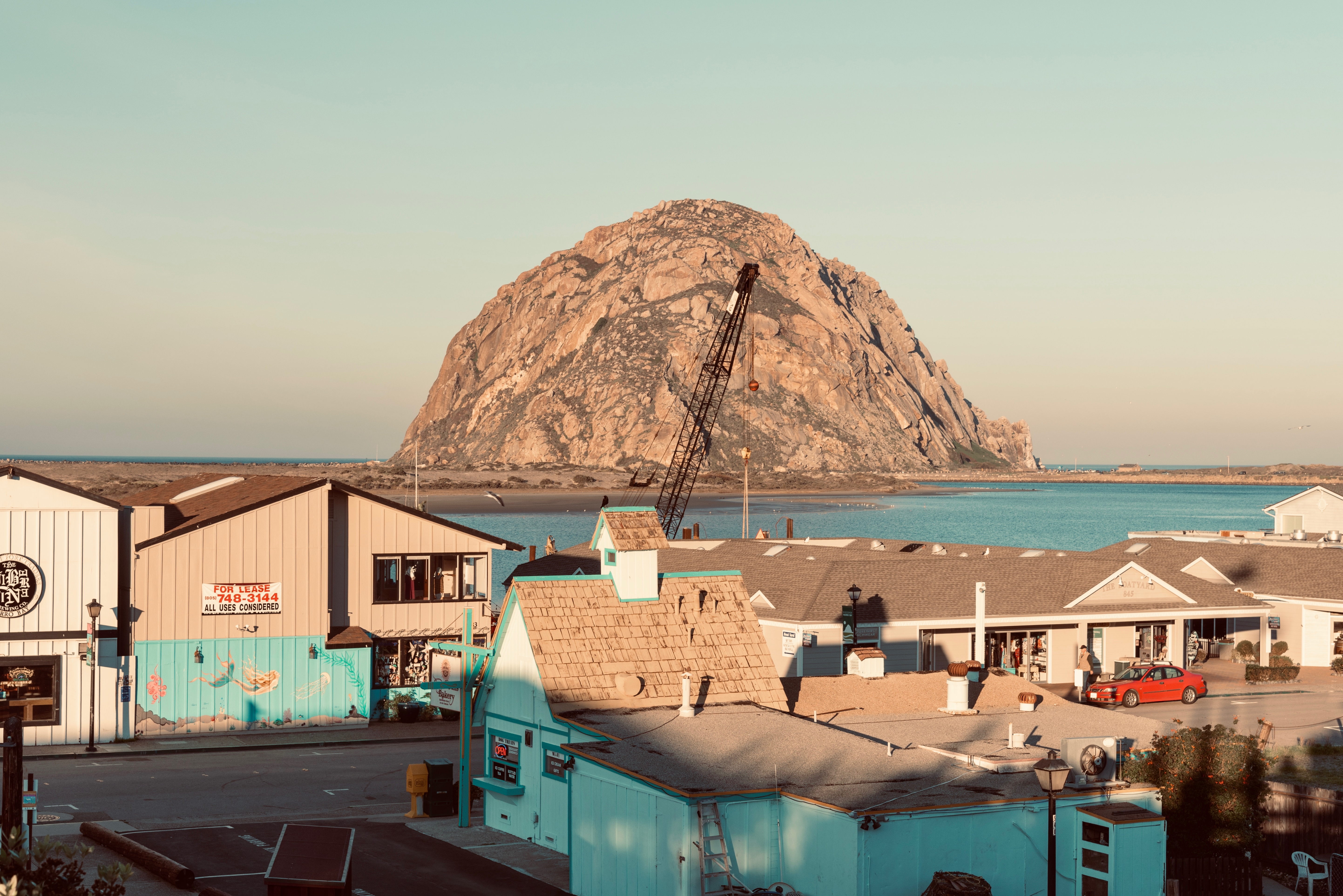 A giant rock protrudes from a bay at dusk. In the foreground, pitched rooftops and colorful buildings.