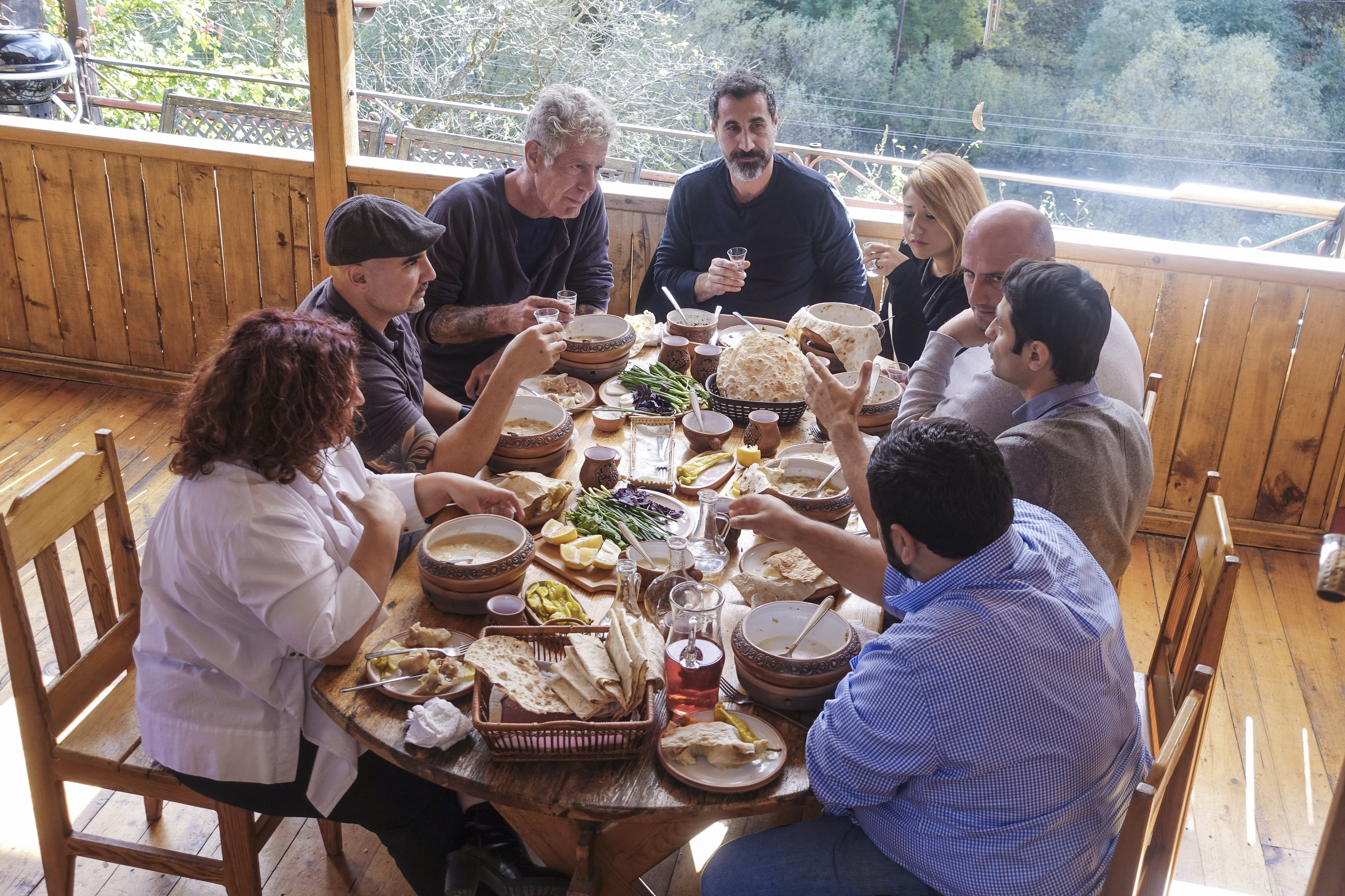 In a scene from this week's Parts Unknown, Anthony Bourdain sits for a meal with guests including musician Serj Tankin at the guest house, Daravand, in Dilijan, Armenia.