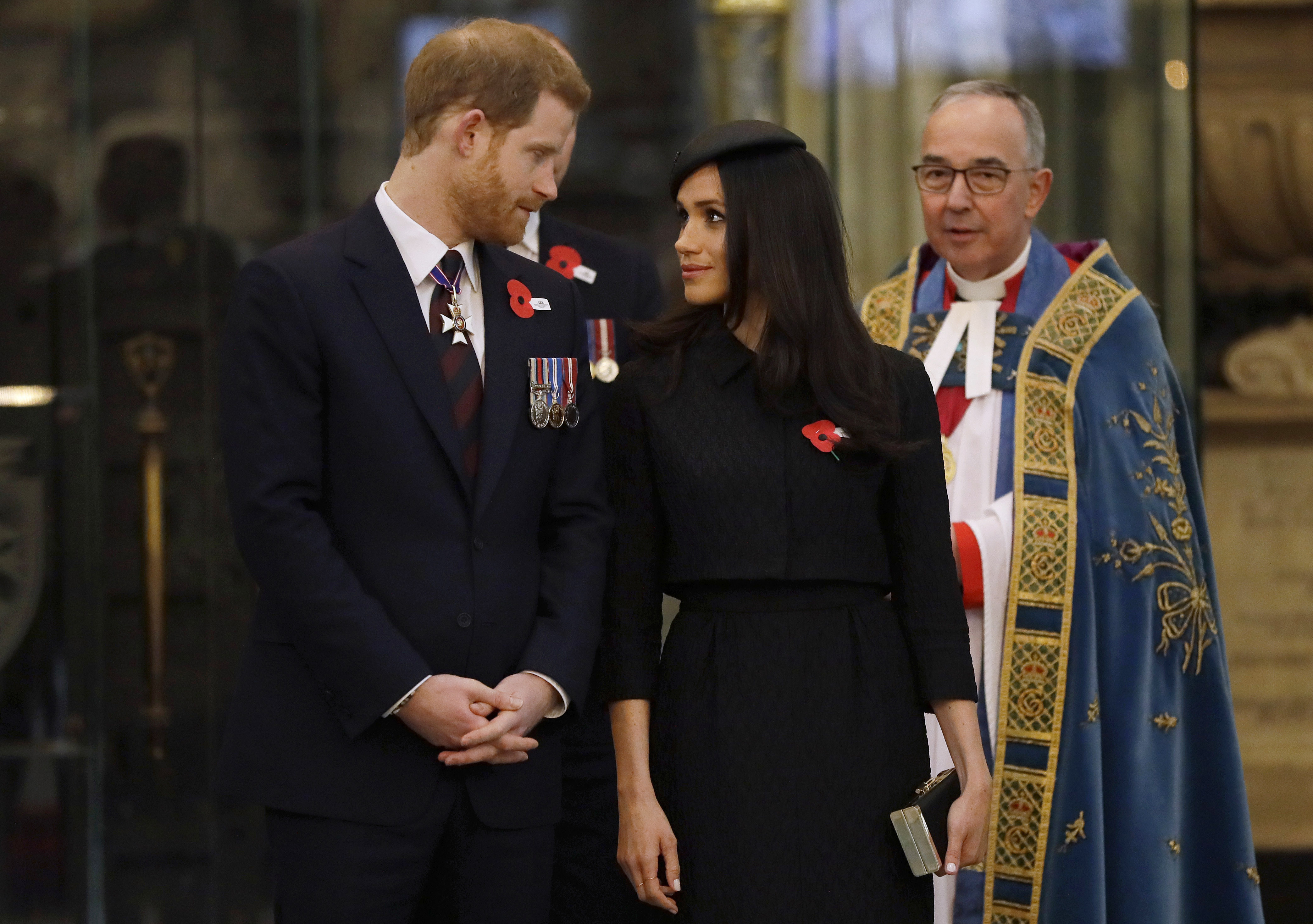 Prince Harry and Meghan Markle look at each other with a priest in the background.
