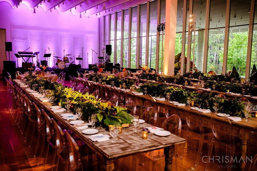 A large wedding reception event space with long tables and a multitude of chairs. The tables have elaborate floral centerpieces and dishes on them. There is a stage at the end of the room which is lit in purple stage lighting.