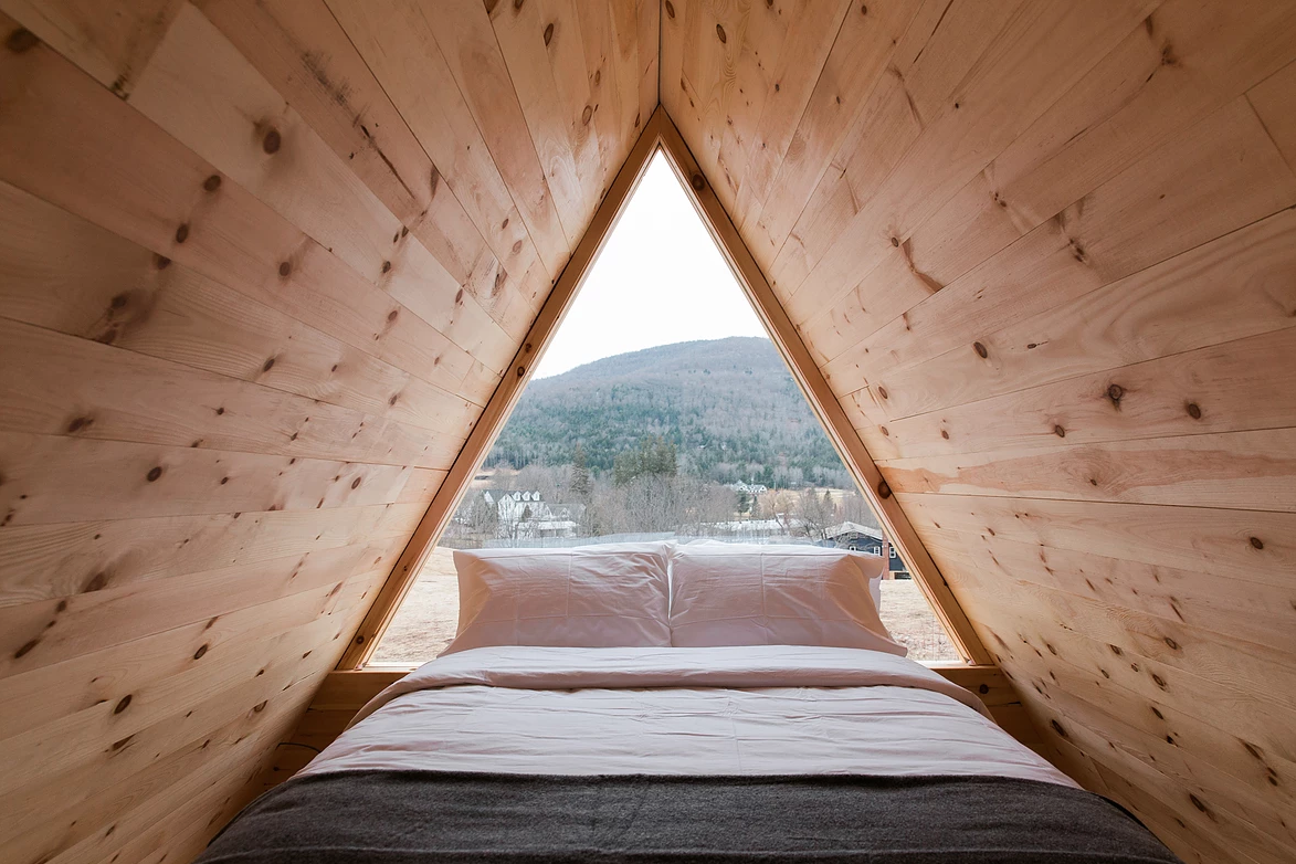 Interior shot of wood-lined A-frame cabin with bed in the window framing mountain views.