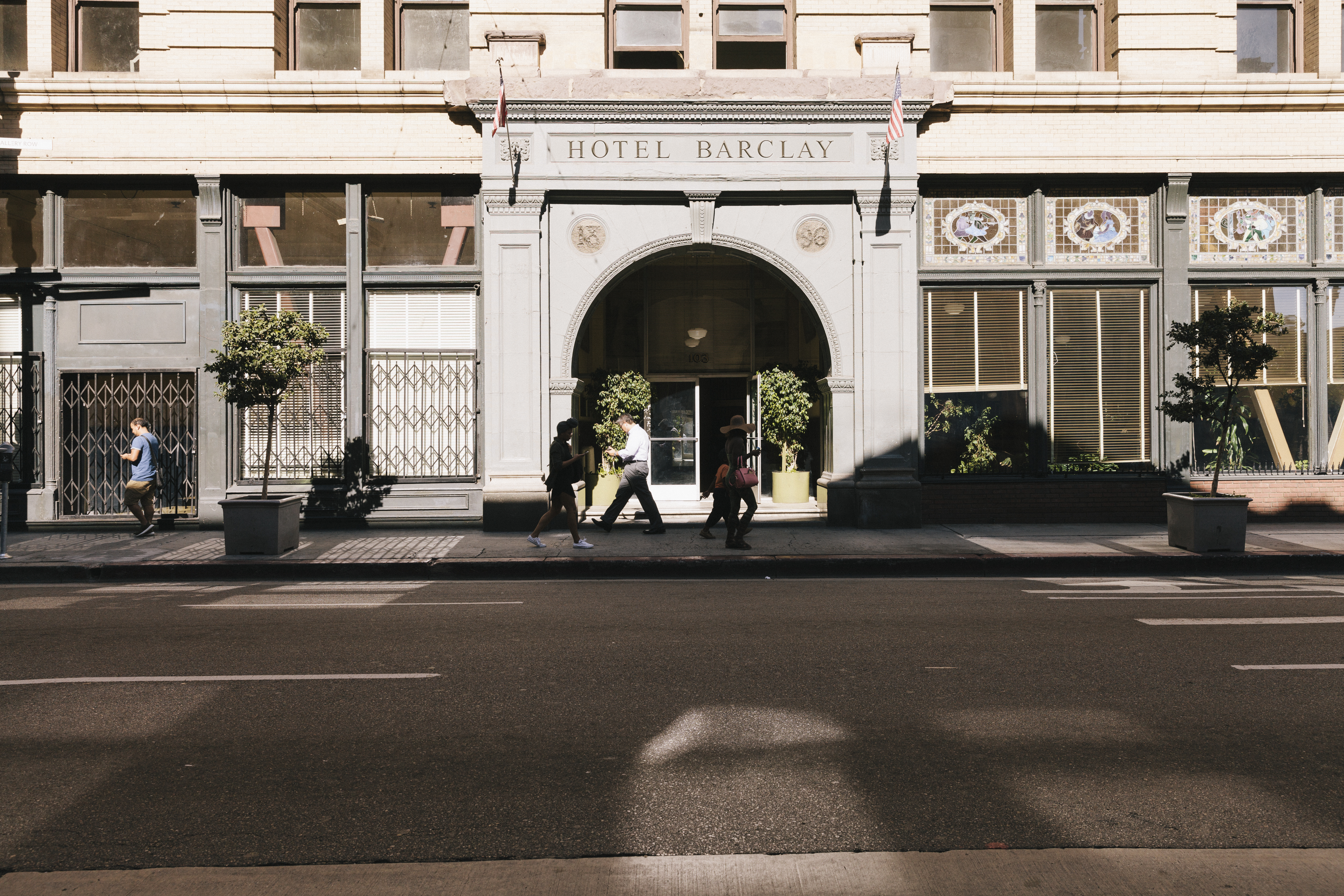 A photo of people on the sidewalk walking by the lettered arch over the entrance to the hotel.