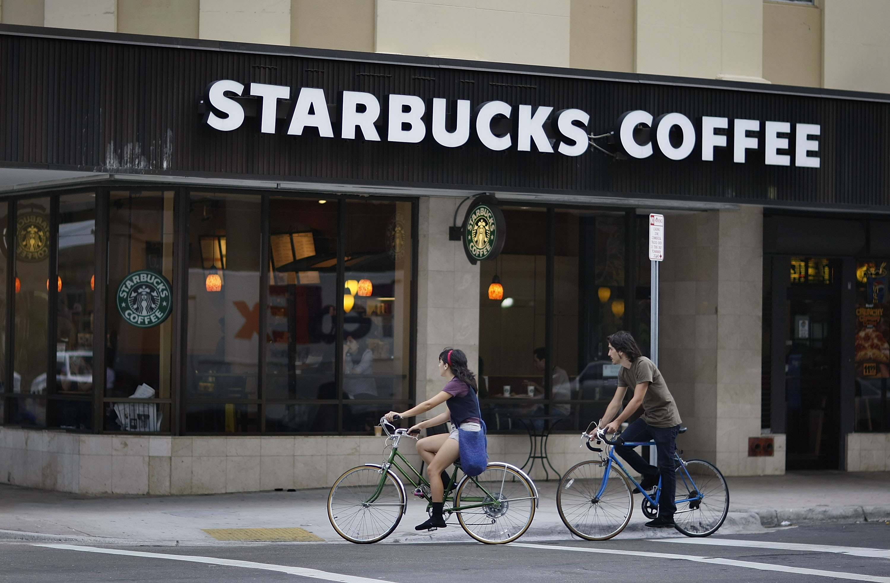 People ride their bikes past a Starbucks Coffee store