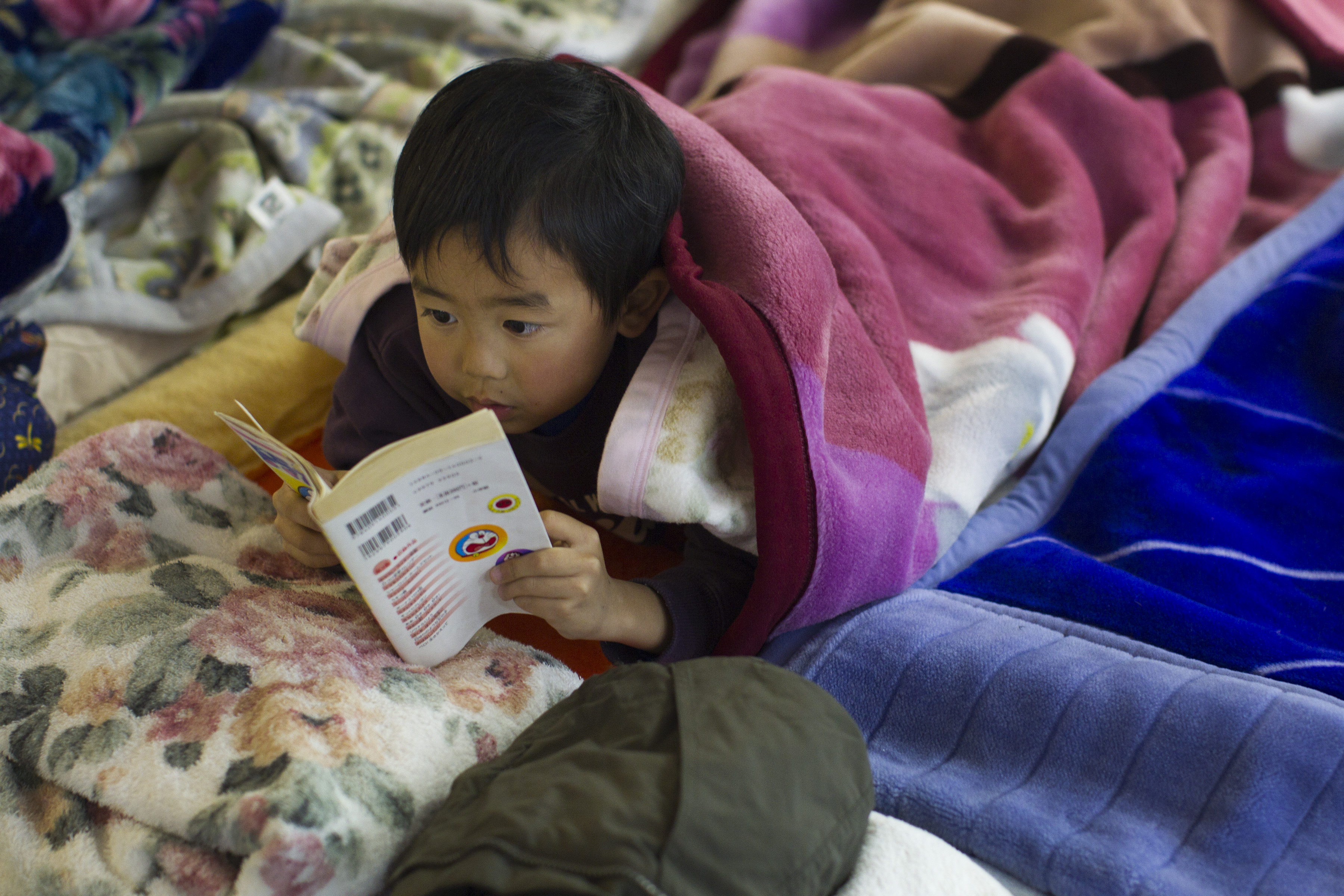 Child in a sleeping bag reading a book