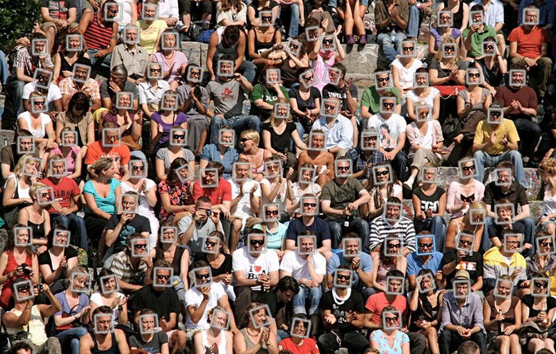A crowd of people sitting in a stadium, each with a superimposed frame on their face