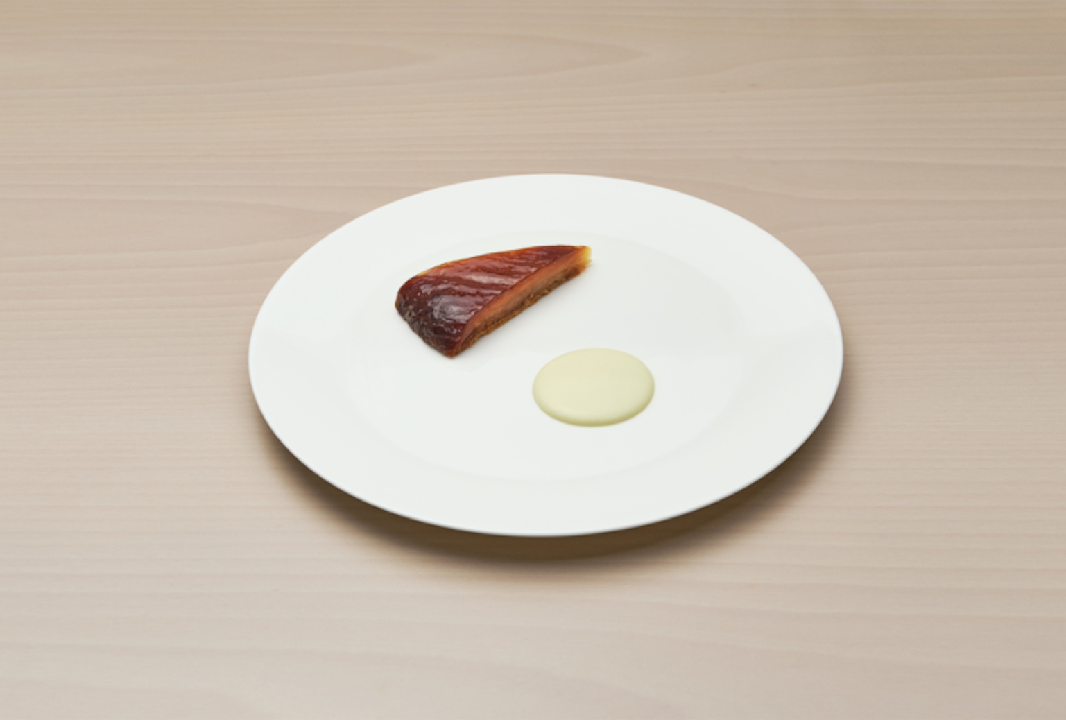 A daikon tarte tatin with a chive cream on a white plate, on a light wood background