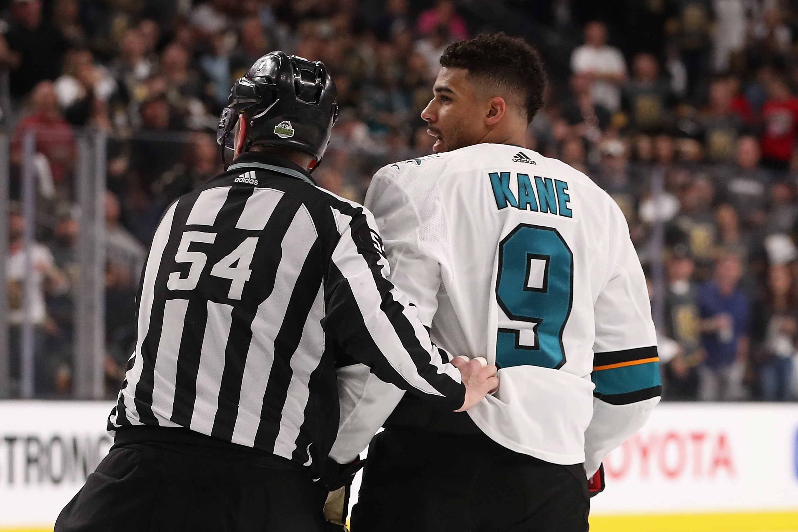 Evander Kane #9 of the San Jose Sharks is escorted off the ice by linesman Greg Devorski #54 after a 5 minute major penalty and game misconduct in the third period Game One of the Western Conference Second Round against the Vegas Golden Knights during the