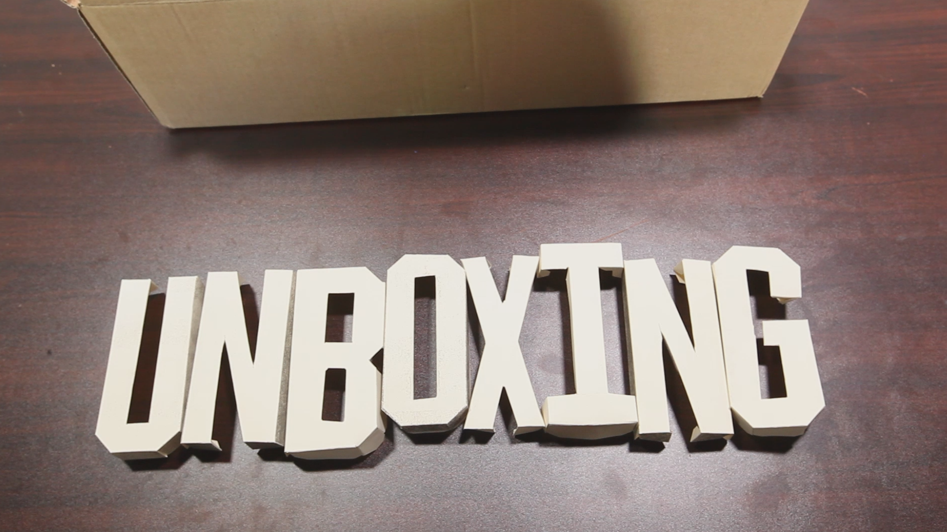 The word UNBOXING, made of cardboard letters, appears on a table.
