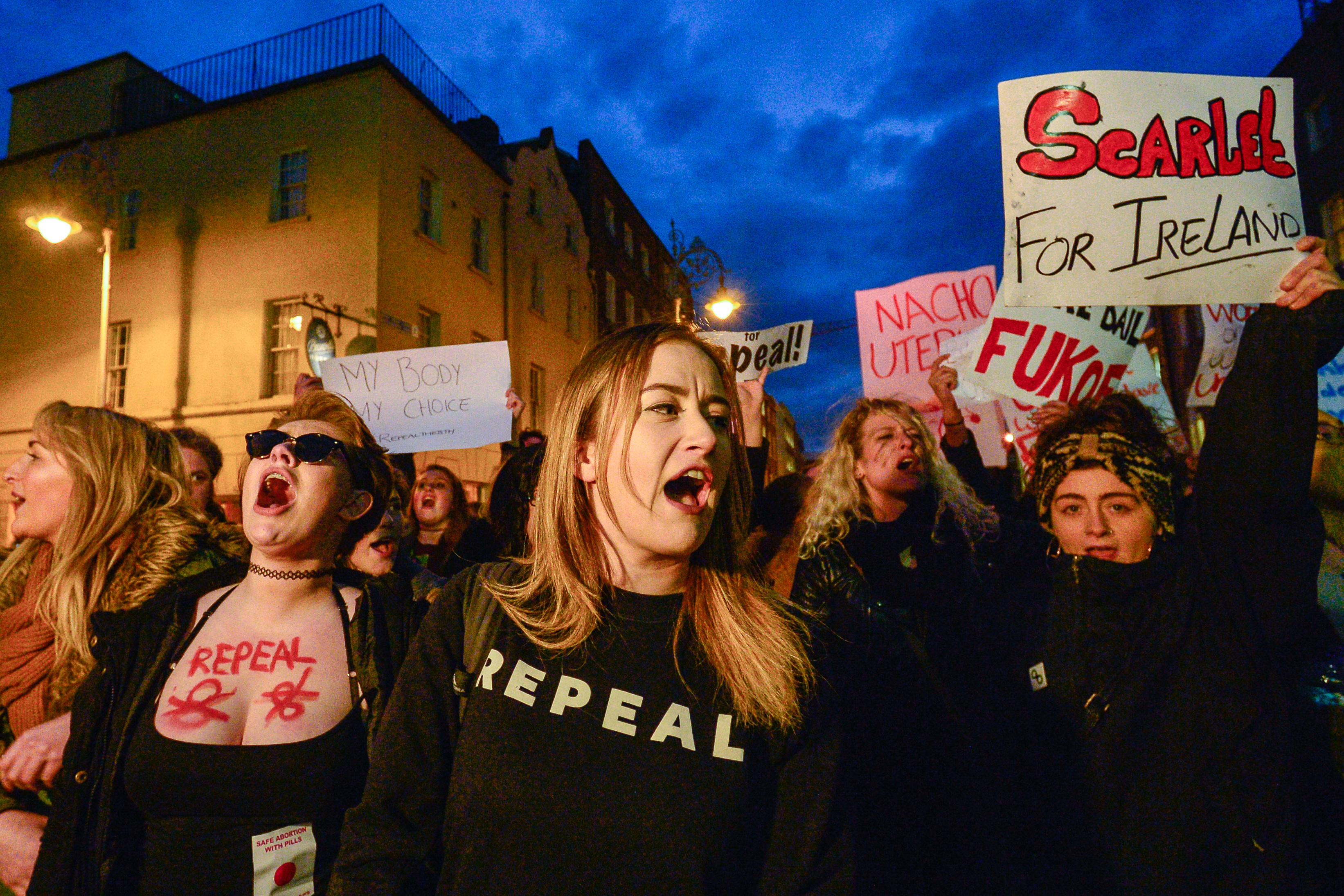 """A group of young women carry signs. In the foreground one wears a black """"Repeal"""" sweatshirt."""