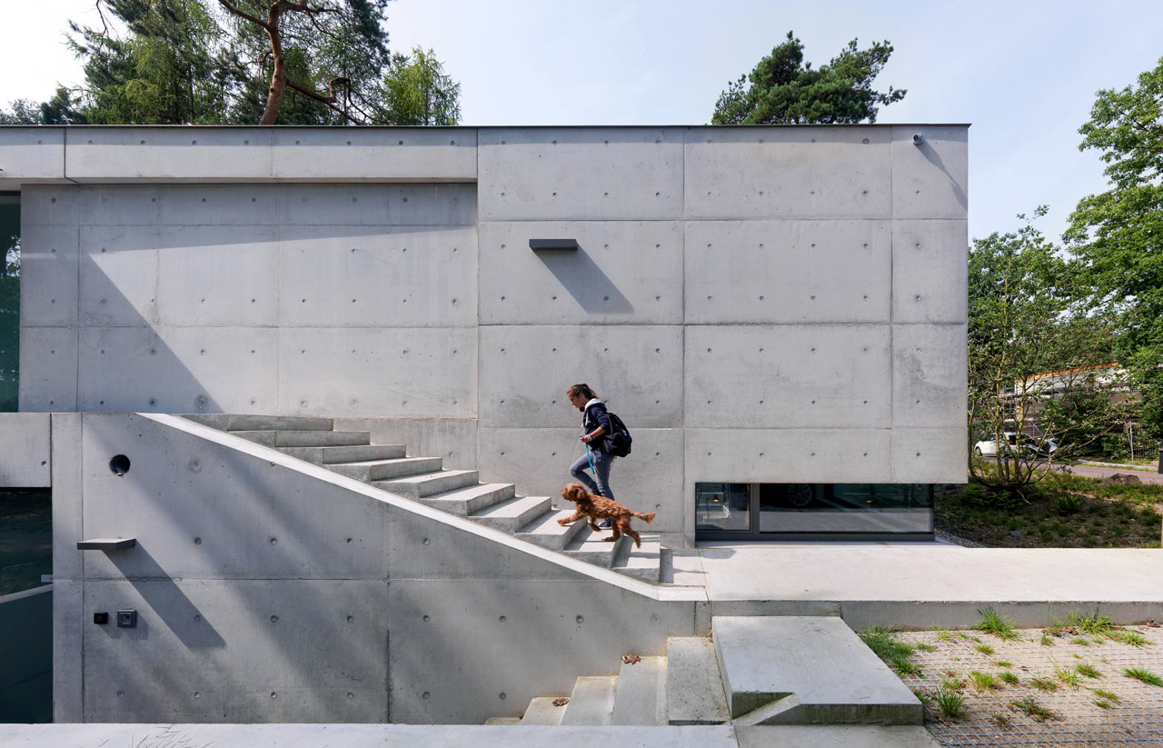 Concrete home with concrete stairs leading to front door