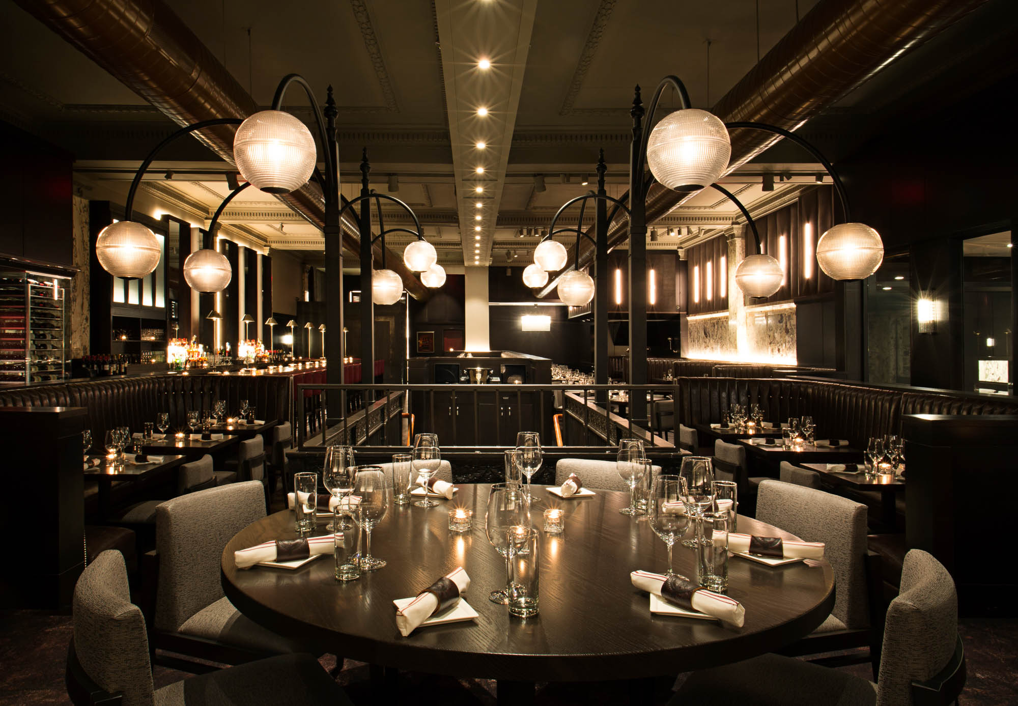 A wide shot of Boston Chops DTX, looking down the length of the restaurant and towards the front door, with elegant light fixtures and a long bar in view
