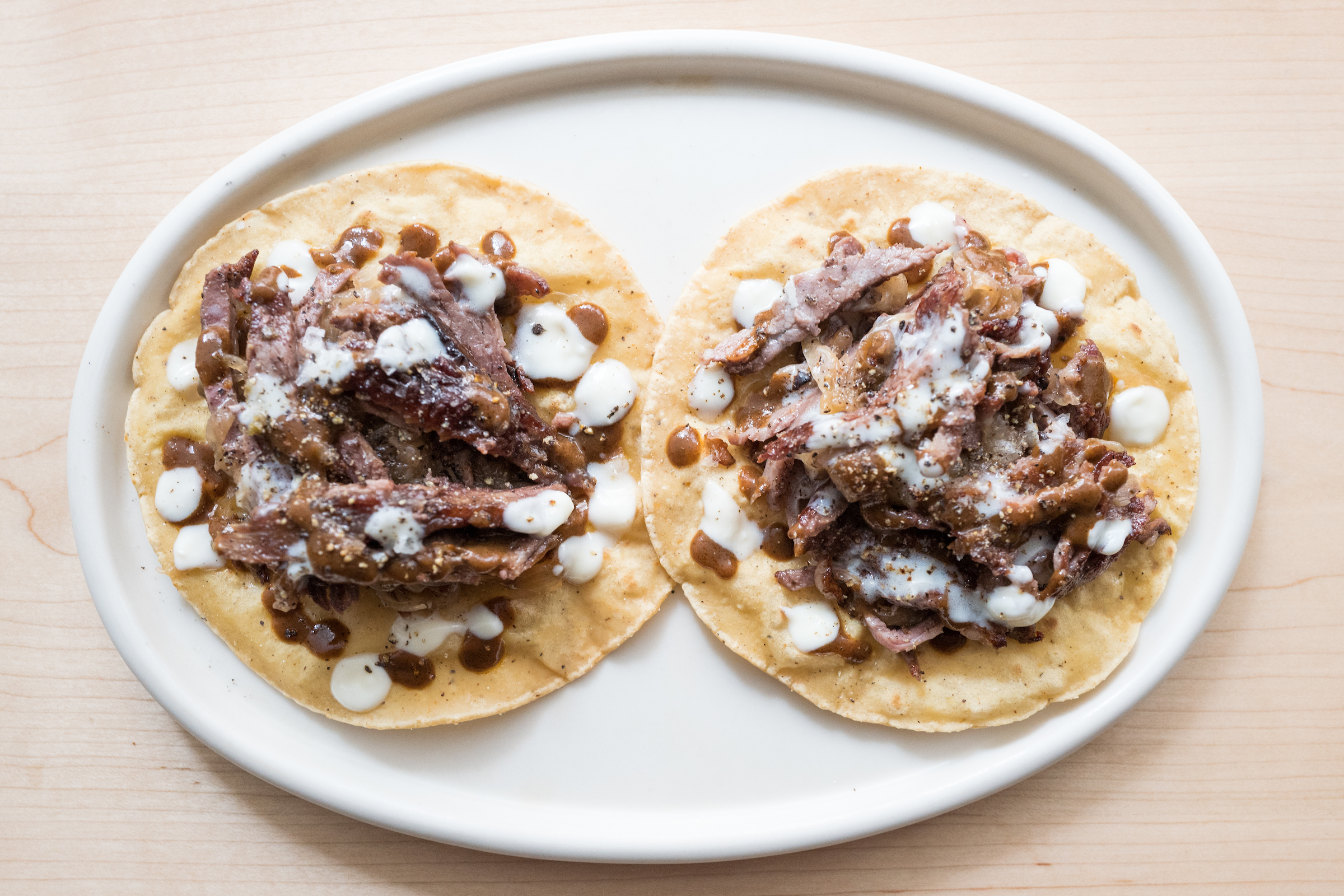 Two tacos with meat and toppings displayed on a white plate on a cream background.